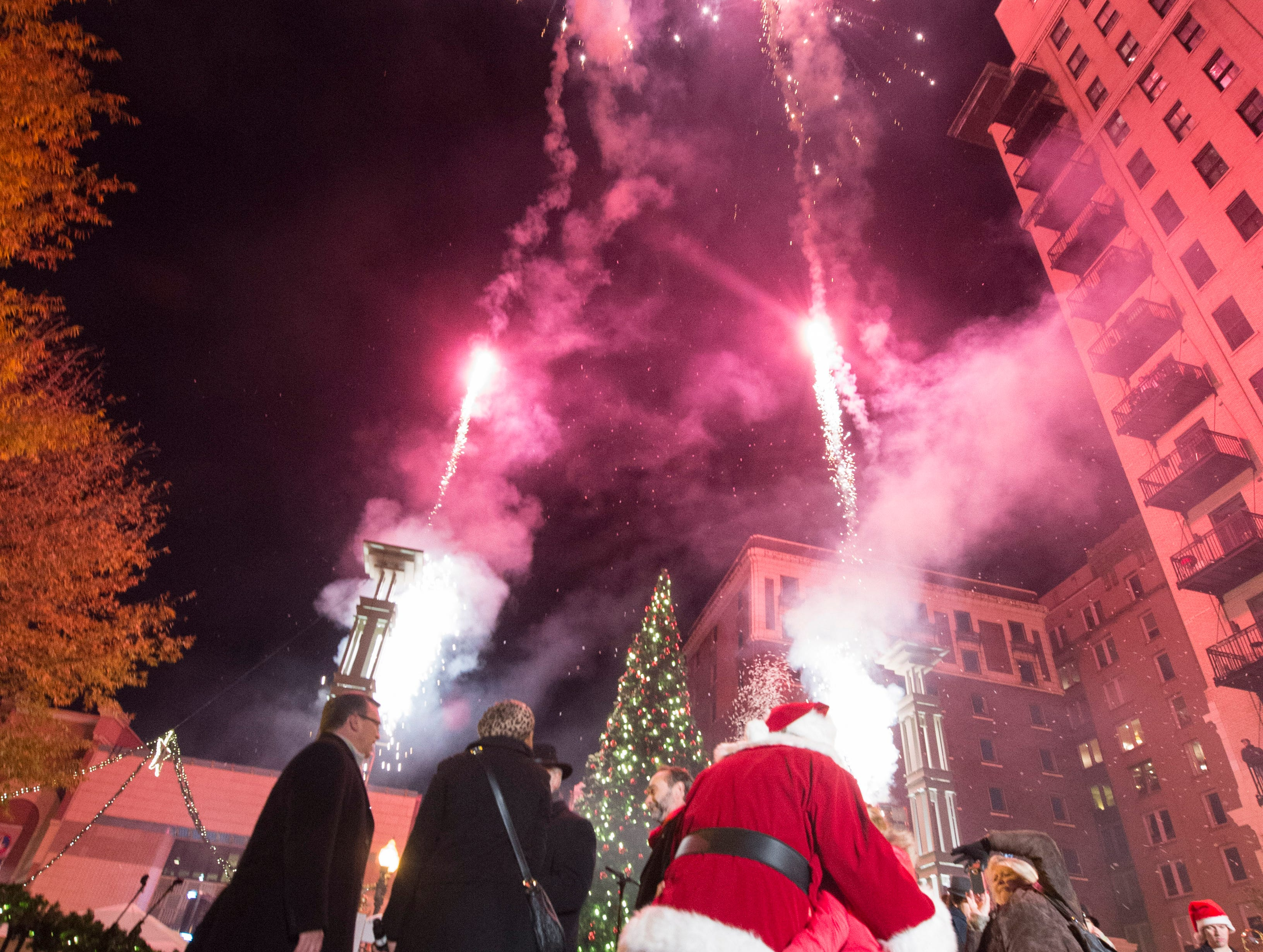 Fireworks shoot up into the sky over downtown Knoxville after the lighting of a 38-foot tall Christmas tree in Krutch Park during Christmas in the City festivities on Friday, Nov. 28, 2014.