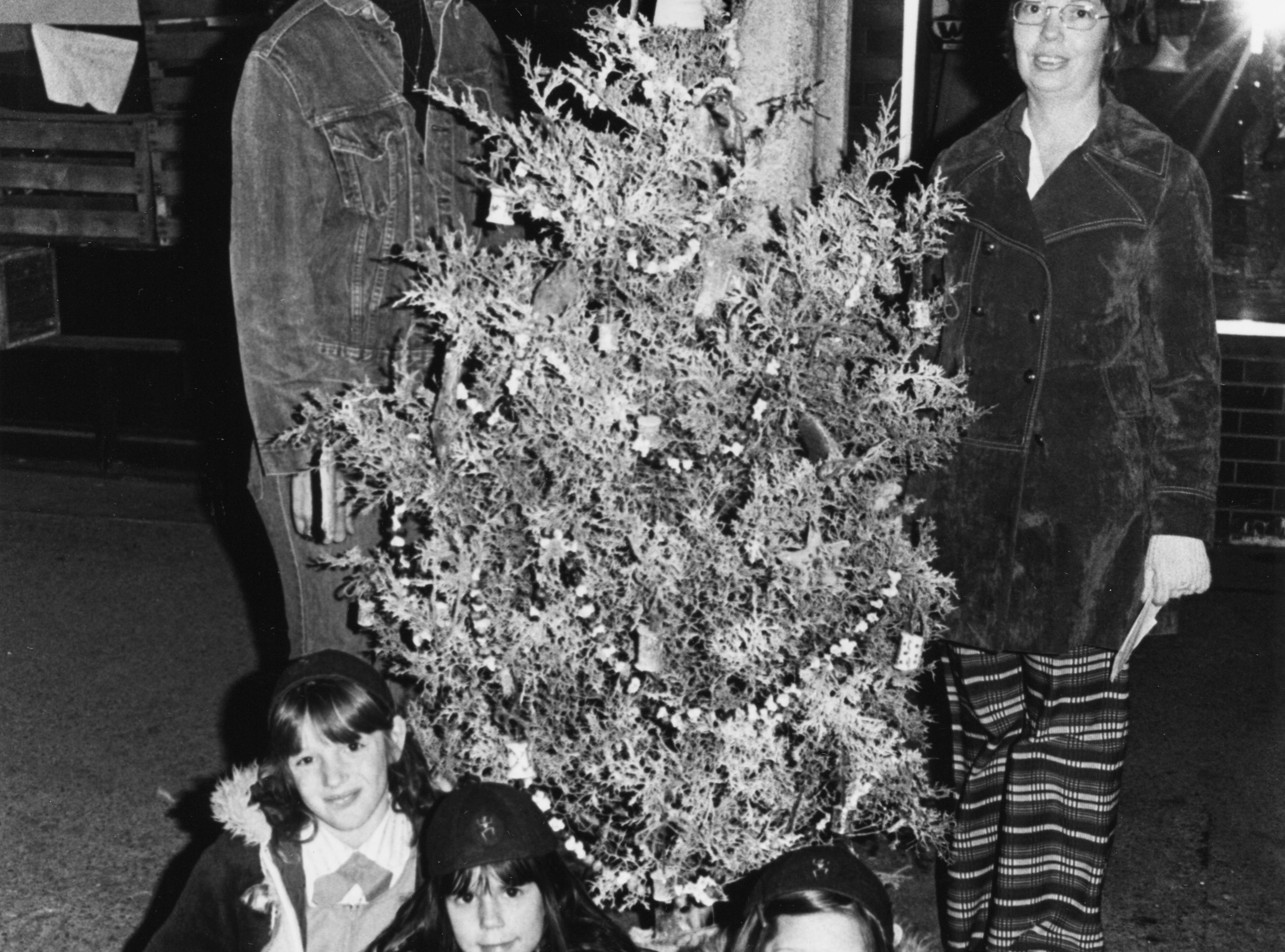 Brownie Troop 387 members Tammy Lynn Shannon, left, Chrise Branch, and Pamela Vaughn show off their first prize entry in the tree decorating contest during the Christmas parade on Dec. 15, 1974. Troop leaders Mrs. Mary Shannon, left, and Mrs. Merle Vaughn are standing.