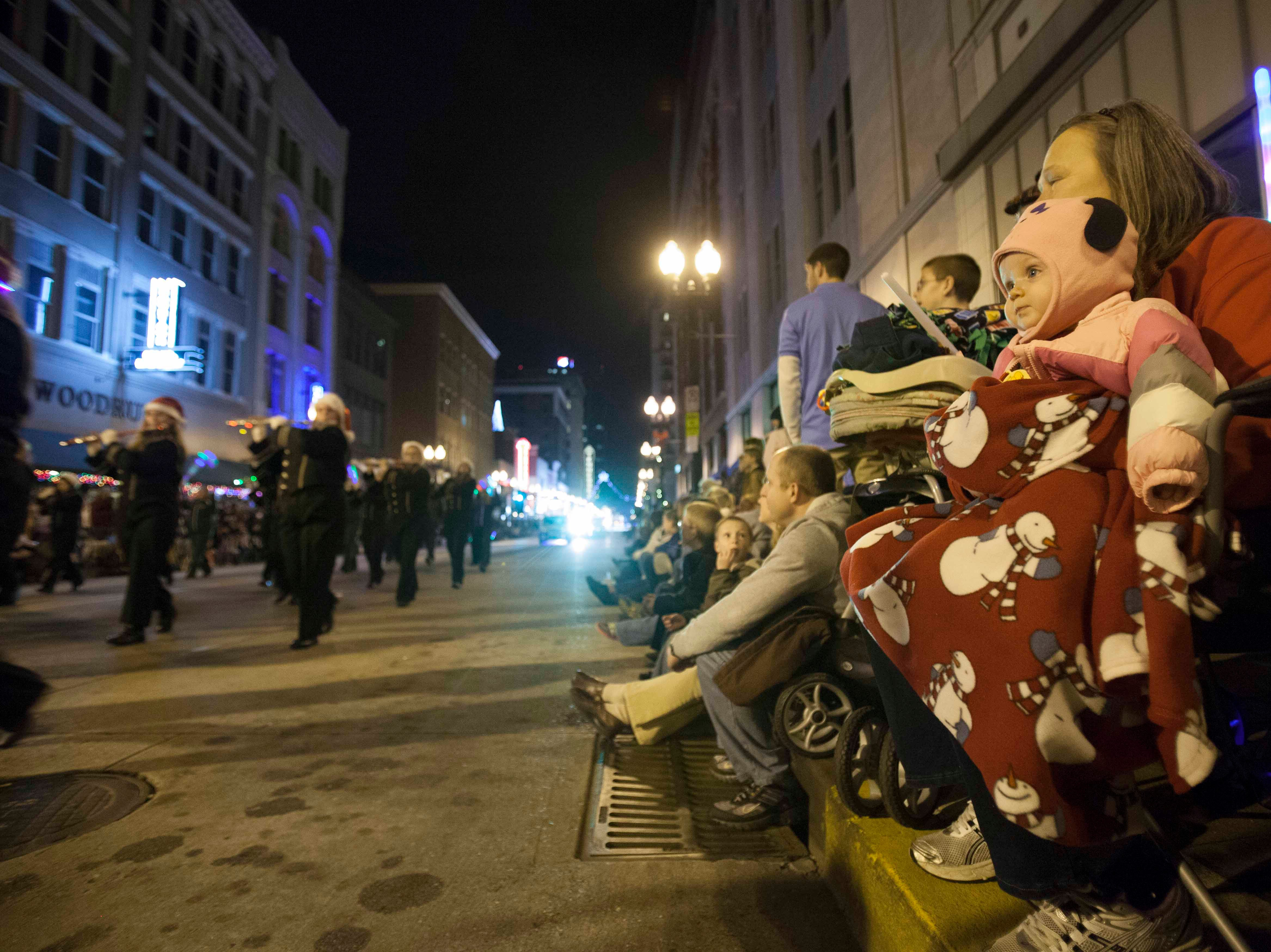 Chandler Bailey, right, watches the Christmas parade on Gay Street downtown as she is held by her grandmother Debbie Chandler, right, Friday, Dec. 7, 2012.