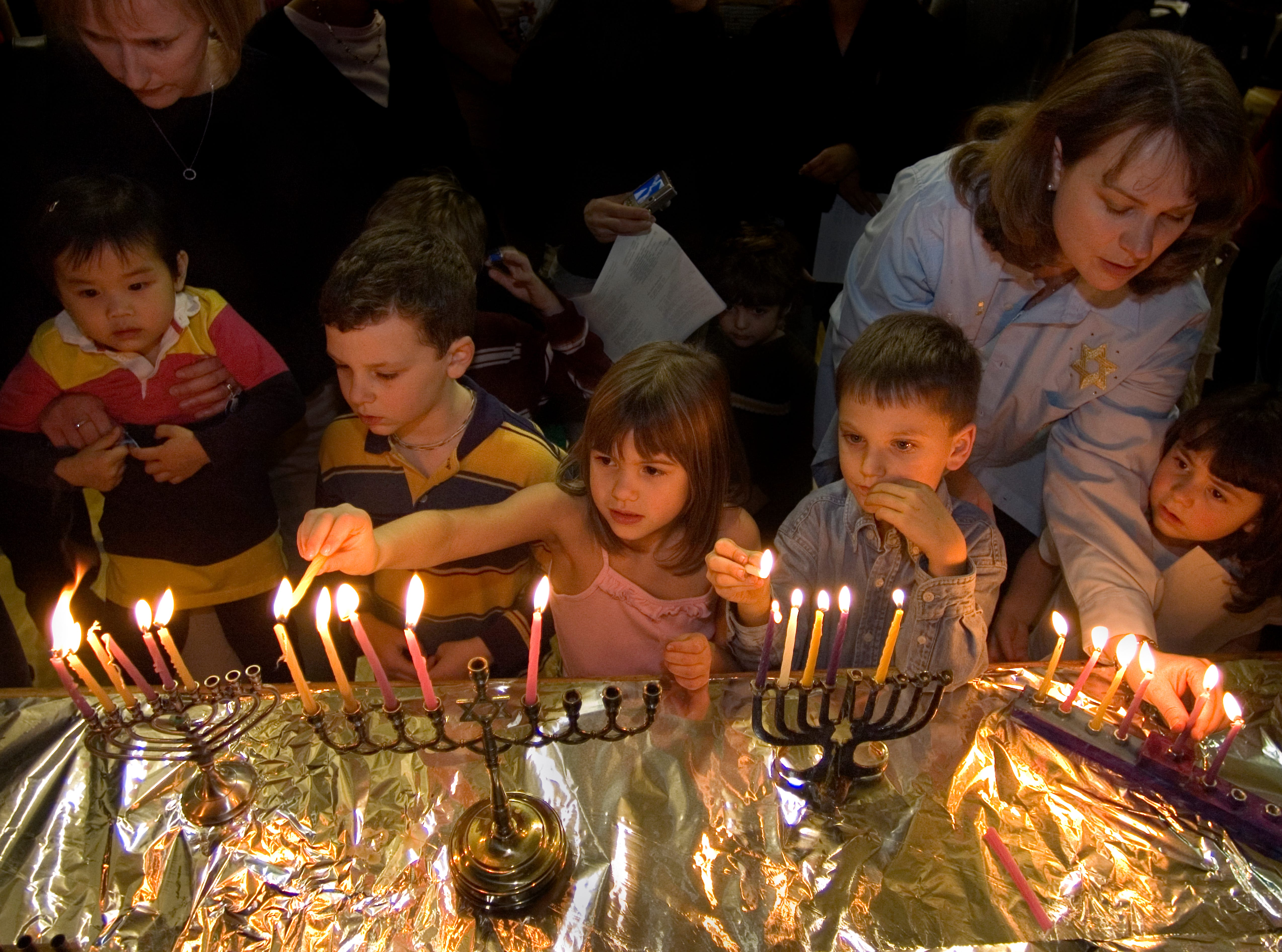 Lorie Hirsh holding her daughter Lily Hirsh, 2, Benjamin Gibbons, 7, Caroline Warman,6, Justen Bain, 6, Melissa Schweitzer and her daughter Lilli Schweitzer, 5, from left, light menorahs during Hanukkah at the Arnstein Jewish Community Center Wednesday. The lighting of the menorah is an important part of this Jewish celebration. Nearly, 2,200 years ago a rebel Jewish Army known as the Maccabees fought to maintain religious practices and the study of the Torah.12/21/06