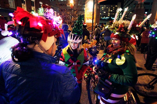 Angela Wampler, right, Paula Hilton, center, and Pam Lee gather at Market Square before riding in the Bike Tour de Lights on Dec. 18, 2015, in Knoxville.