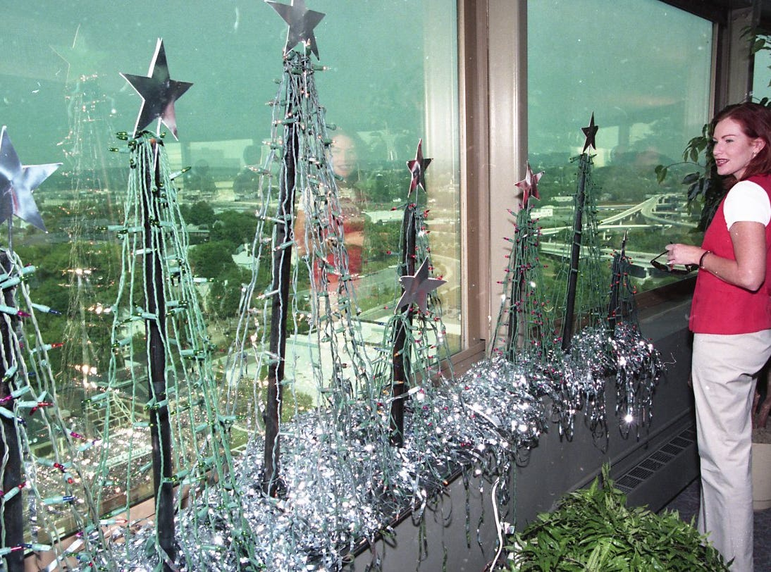 "Emily Fisher of the Knoxville Area Chamber Partnership looks at a Christmas tree display in the Sunsphere at World's Fair Park before a press conference in August 1998 where Mayor Victor Ashe announced that Knoxville's ""Up on the Rooftops"" Christmas display has grown from 11 trees on five buildings four years ago will grow to more than 100 trees in 1998, including a 50-foot lighted tree atop First Tennessee Plaza Tower."