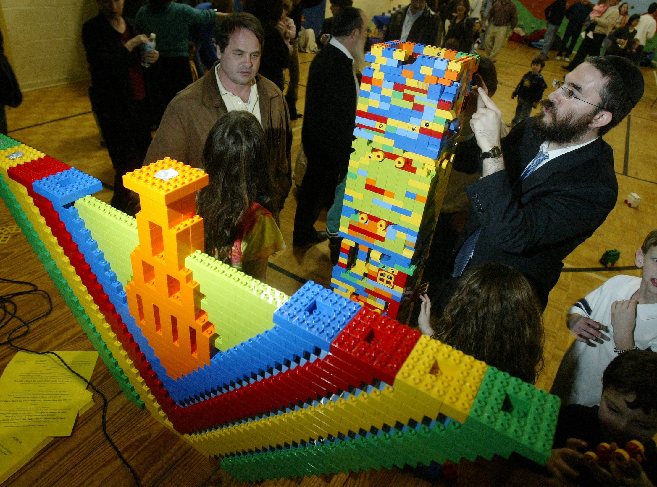 Rabbi Yossi Wilhelm assembles the sections of the base that will hold the menorah during a Hanukkah festival held at the  Arnstein Jewish Community Center. The children used building blocks to make a 10-foot menorah. 12/28/05