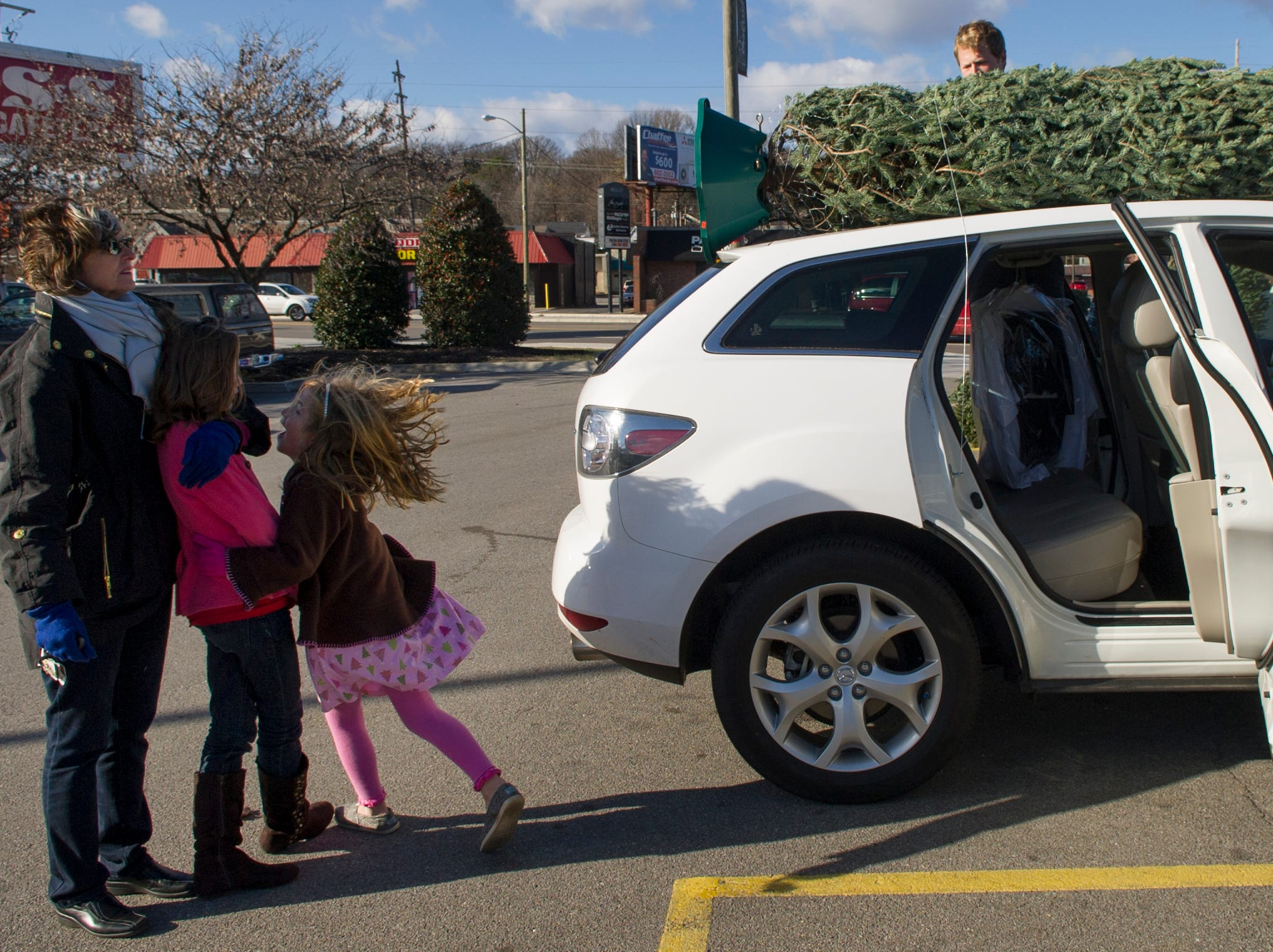 Jean Galyon, left, looks on as Mayo Garden Center employee Jeff Rizy, right, ties a Christmas tree to her car while her grandchildren, Mary Kate and Claire Holladay, left to right, look on at the store Friday, Dec. 21, 2012.
