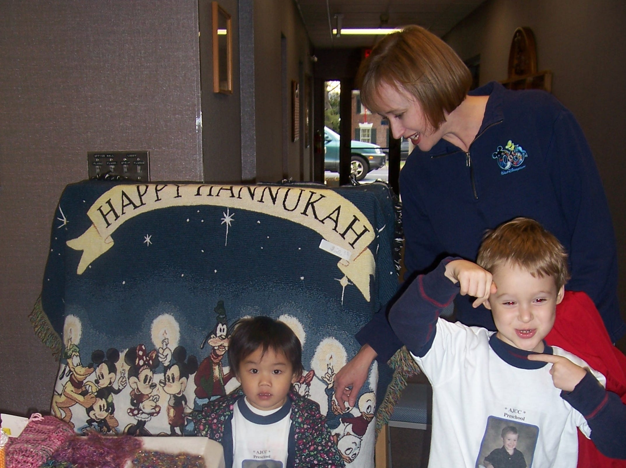 Lorie Hirsh and her children, Ben Hirsh, 4,and Lily Hirsh, 2, are making the rounds of the Chanukah Crafts Bazaar sponsored by the Sisterhood of Temple Beth El. The youngsters were quite taken with a Disney Happy Hanukkah throw.