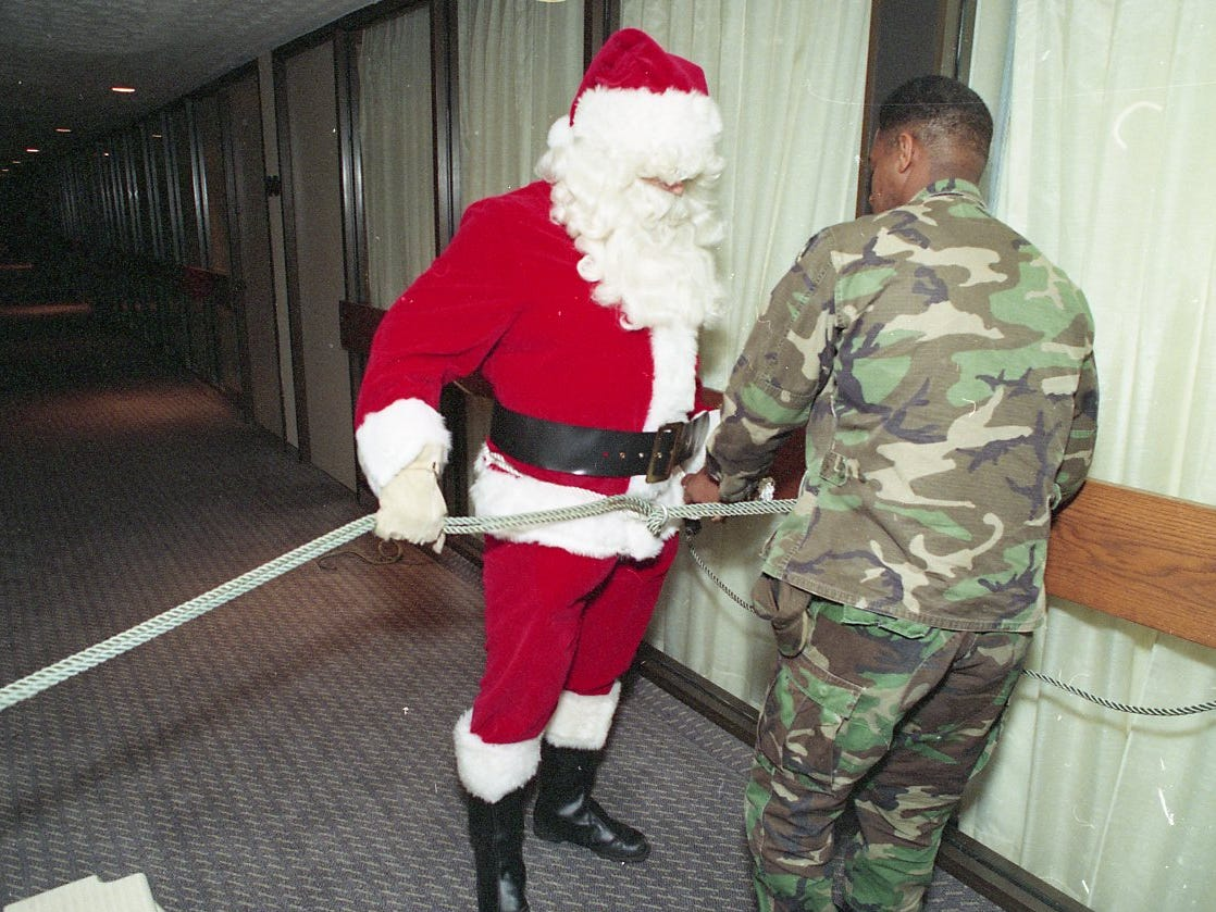"Sgt. Robert Carpenter helps Sgt. Santa Claus get ready to repel off the balcony of the Hyatt Hotel into the lobby for the opening of ""Christmas in the City"" celebration kickoff in December 1993."