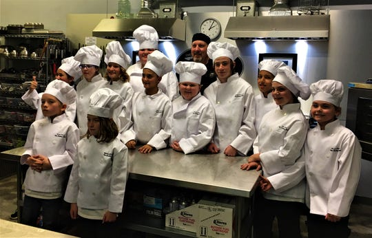 Chef John Alunni, in black, proudly stands behind the Master Chef Junior graduating class in November.