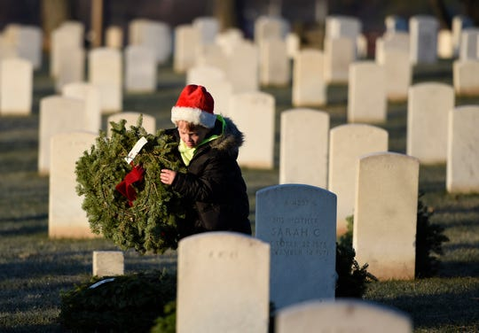 Avery Lewis, 6, lays a Christmas wreath on a grave in Knoxville National Cemetery on Saturday, Dec. 13, 2014. Volunteers participated in wreath-laying ceremonies throughout the day as part of a Wreaths Across America effort at three local veteran cemeteries.