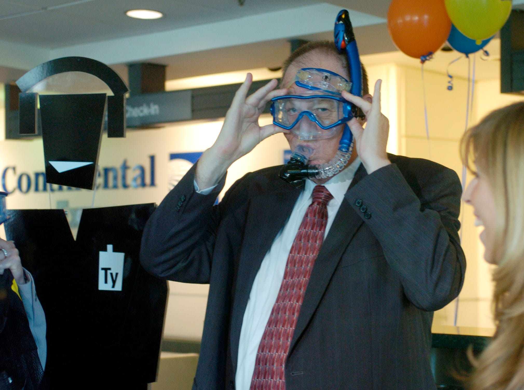 MKAA President Bill Marrison tries on a snorkeling mask Wednesday that is a gift from Tyri Squyres (CQ), right, of Allegiant Air at McGhee Tyson Airport in September 2006.