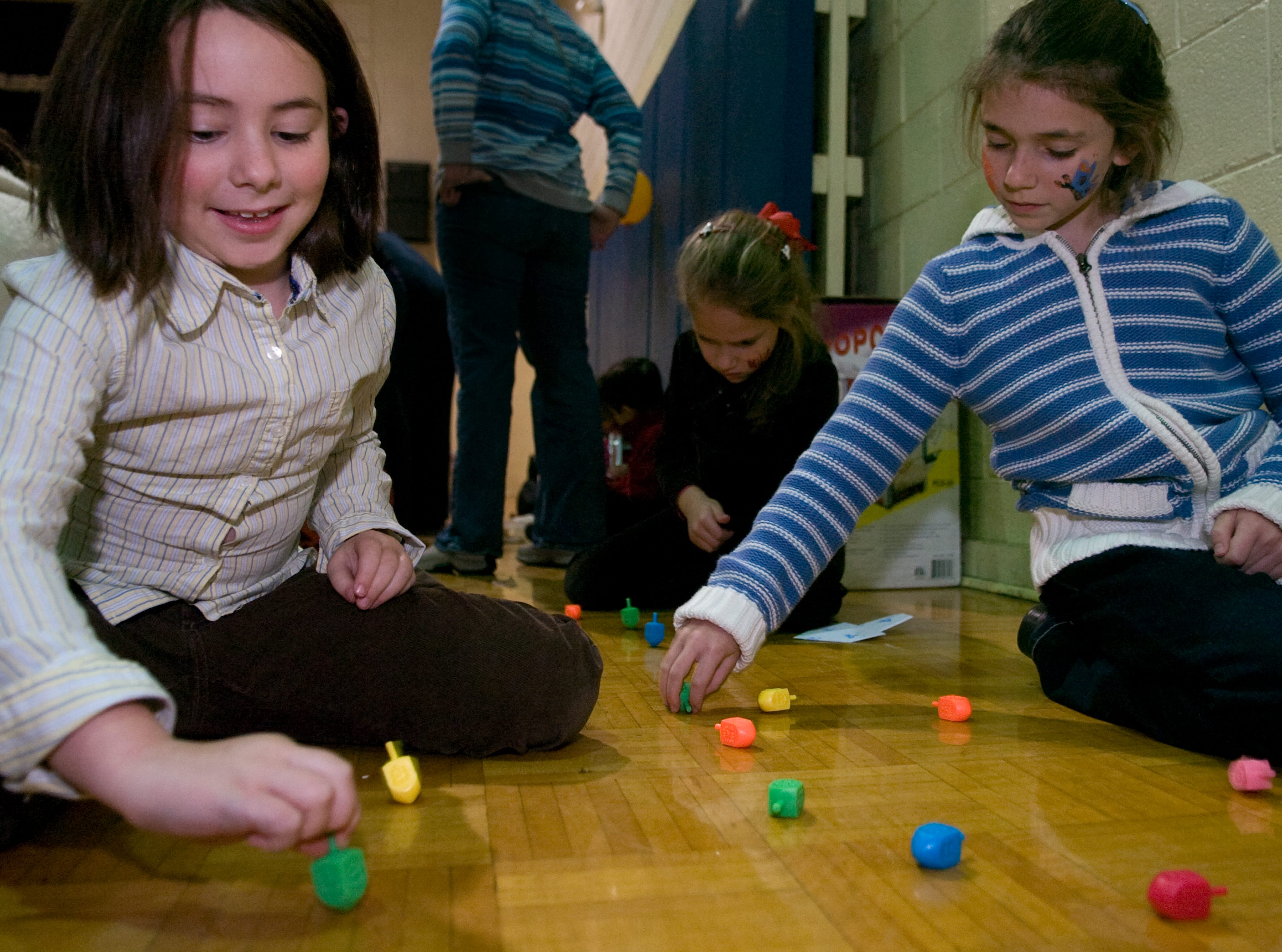From left, Lillian Schweitzer, 8, Tifannie Rosen, 6, and her sister Arielle Rosen, 9, spin dreidels on Sunday, Dec 13, 2009 at the Arnstein Jewish Community Center during the third annual Menorah Madness celebration. The event collected donations of canned goods to be given to Second Harvest Food Bank.