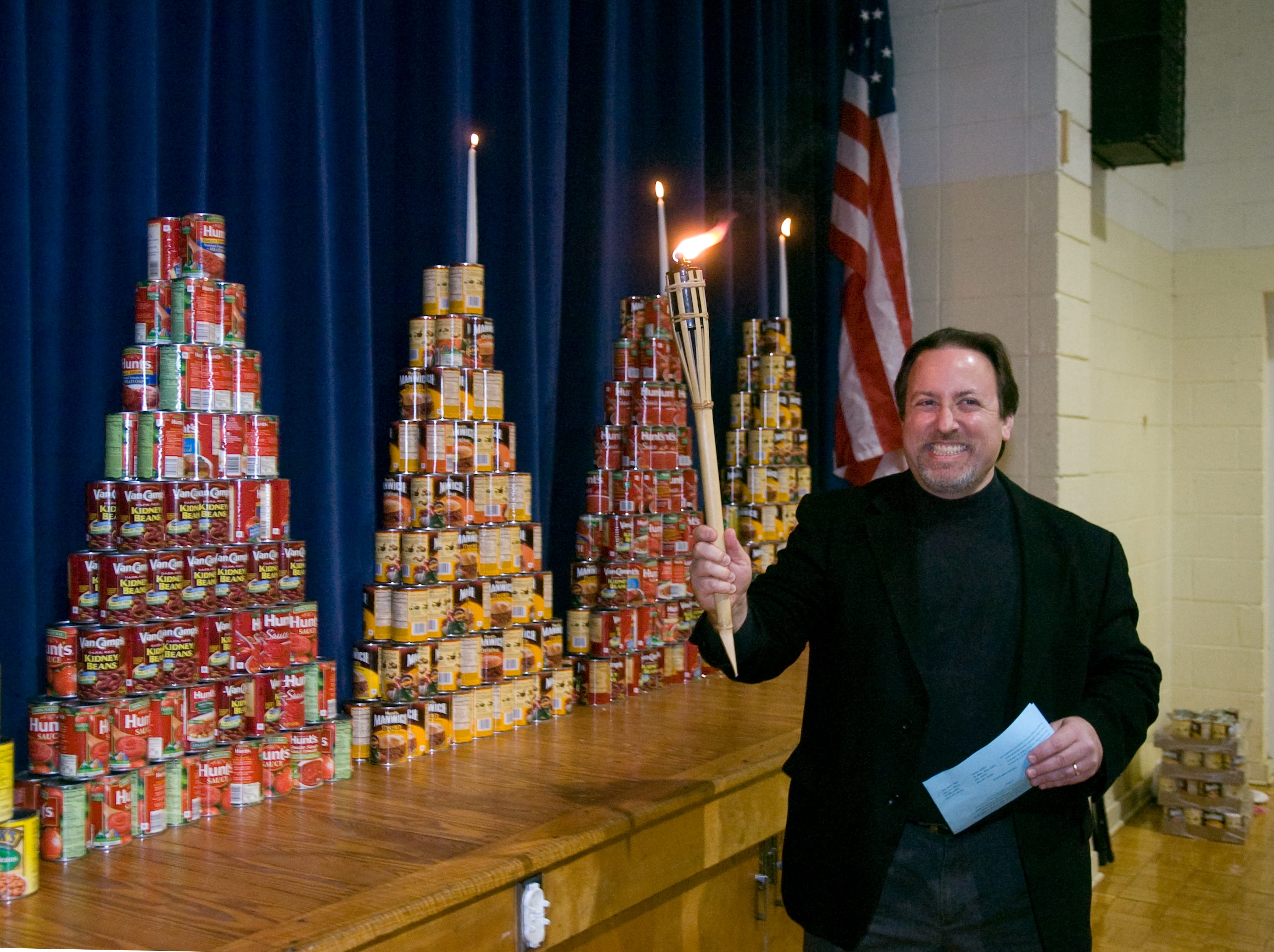 Music Director of the Knoxville Symphony Orchestra, Lucas Richman smiles after lighting three candles on a menorah constructed of donated cans of food on Sunday, Dec 13, 2009 at the Arnstein Jewish Community Center. The event is the third annual Menorah Madness which collected cans of food that will be donated to Second Harvest Harvest Food Bank.