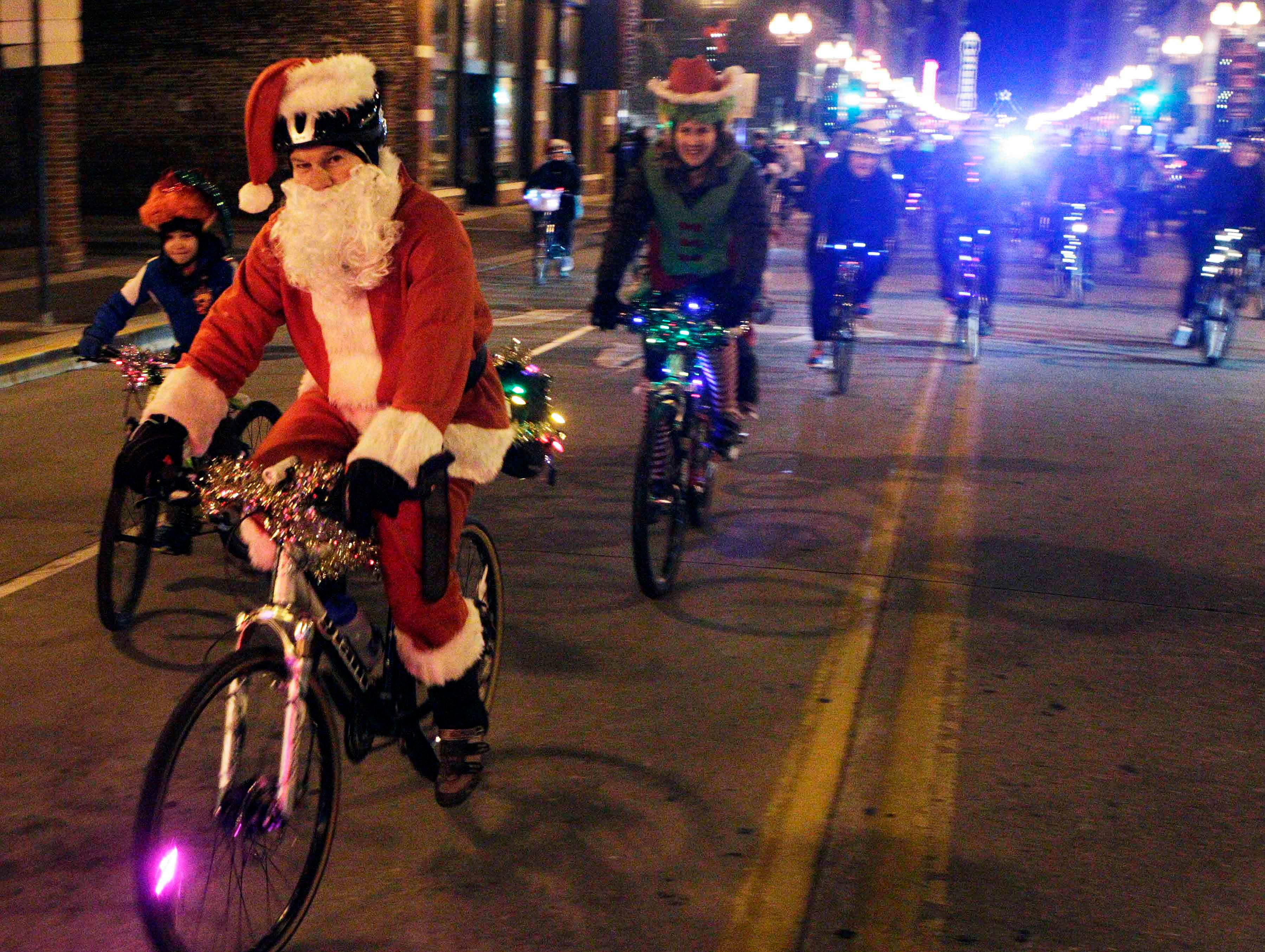 Riders with bikes decorated with Christmas lights and wearing costumes make their way down Gay Street during the Bike Tour de Lights Friday, Dec. 18, 2015, in Knoxville, Tenn.
