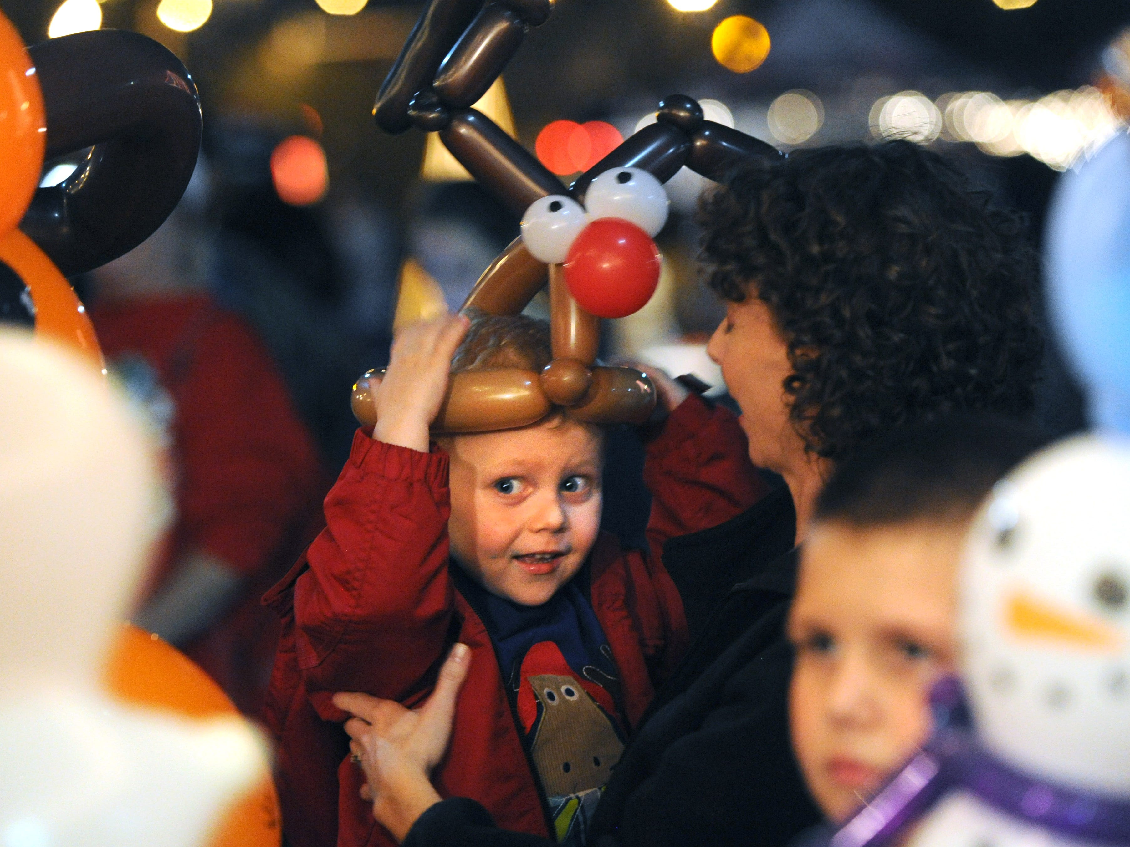 Gavin Peairs, 3, center, dons a reindeer balloon hat as he is held by mother Melinda Peairs during Xfinity Christmas at Chilhowee Park on Friday, Dec. 11, 2015. The event also featured gingerbread house-making, marshmallow roasting, and photos with Santa Claus.