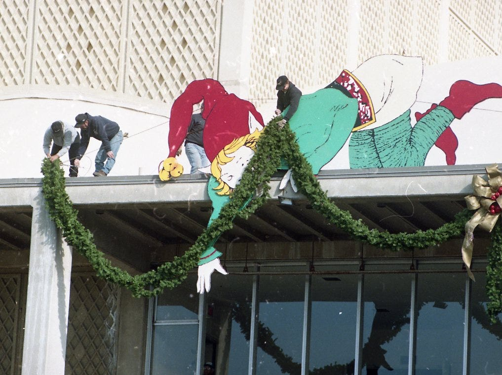 Knoxville city employees give one of Santa's helpers a helping hand as they get Christmas decorations into place on the roof of the Civic Coliseum in November 1996.
