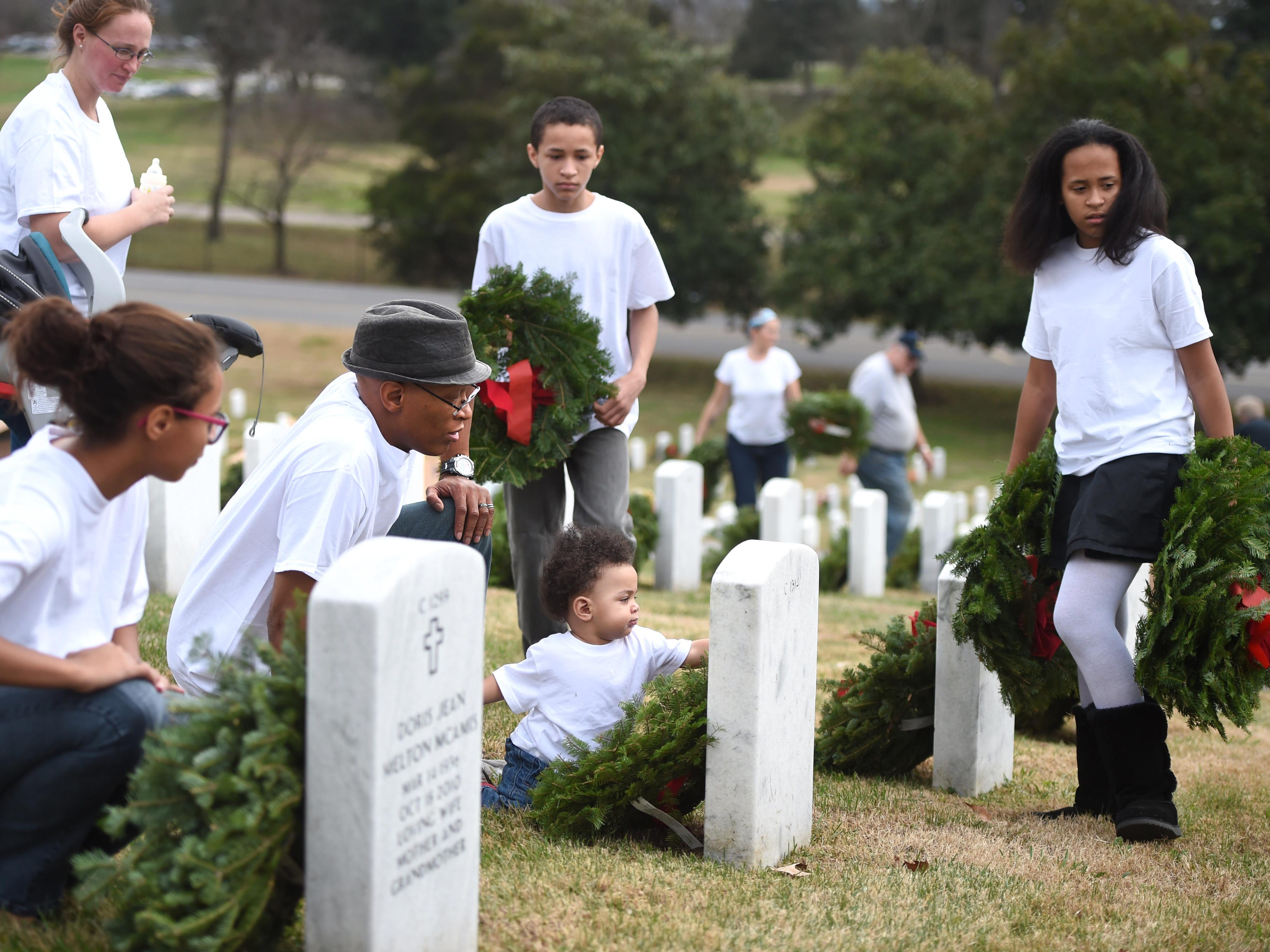 Shamare Johnson, 1, center, helps lay holiday wreaths on headstones with, from left, sister Sheyenne, mother Rebikah, father Sharles, brother Shaque, and sister Shentasia at East Tennessee State Veterans Cemetery on Saturday, Dec. 12, 2015. Sharles Johnson's grandfather served in the military and he brought his entire family out to participate in Wreaths Across America's event.
