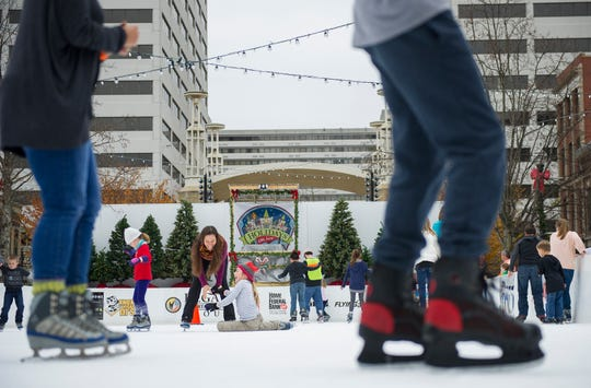 Gina Brace, center, laughs as she helps her daughter Gigi Brace, 9, after she fell during opening weekend for the Market Square ice skating rink Nov. 28, 2015.
