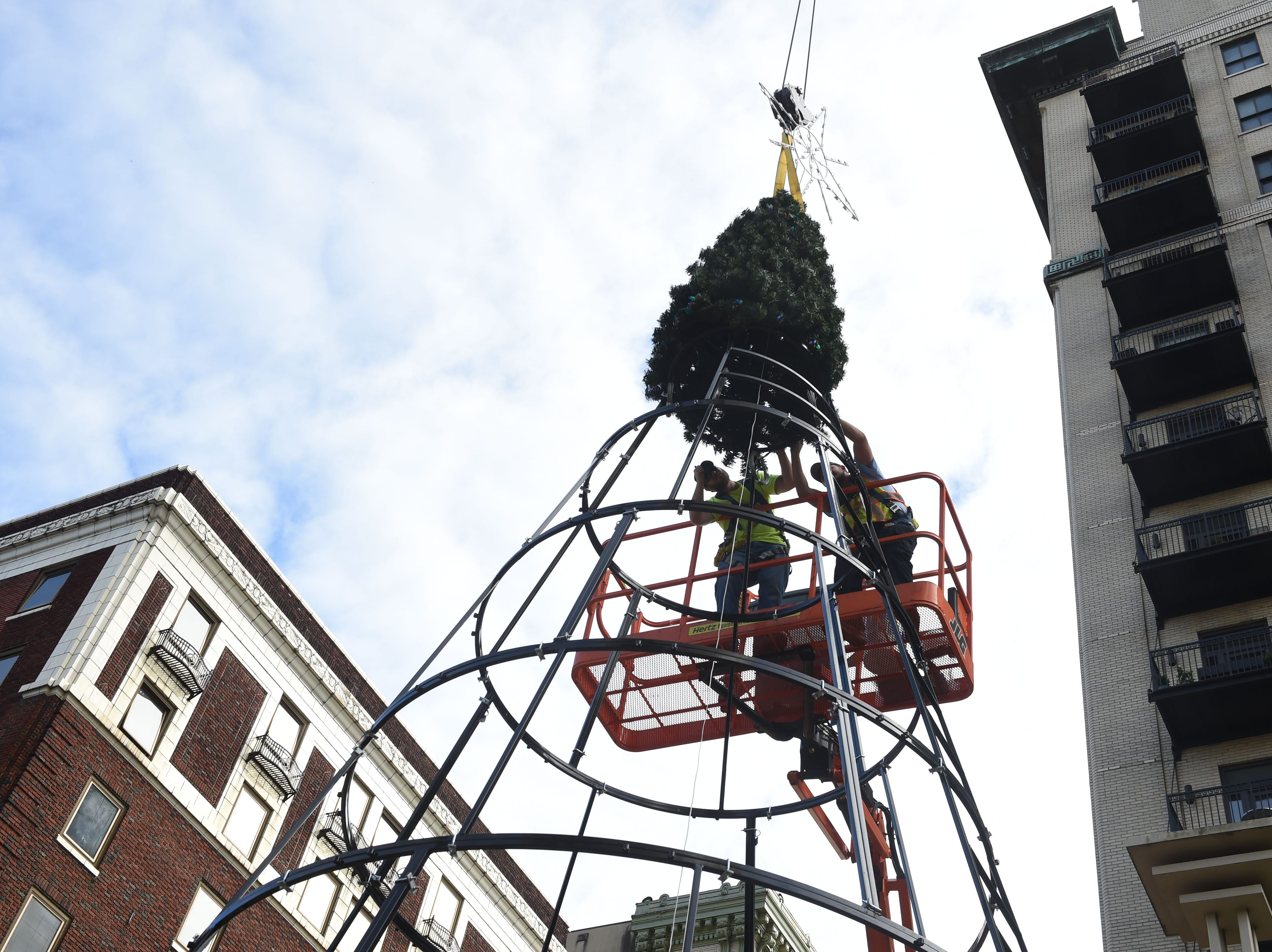 City of Knoxville Public Service workers Cody Foster, left, and Nick Andreasen place the top of a 42 foot decorative holiday tree in Krutch park in downtown Knoxville Tuesday, Nov. 3, 2015. Workers began constructing the new tree on Monday, which will be lit during the Regal Celebration of Lights on November 27th at 6pm.