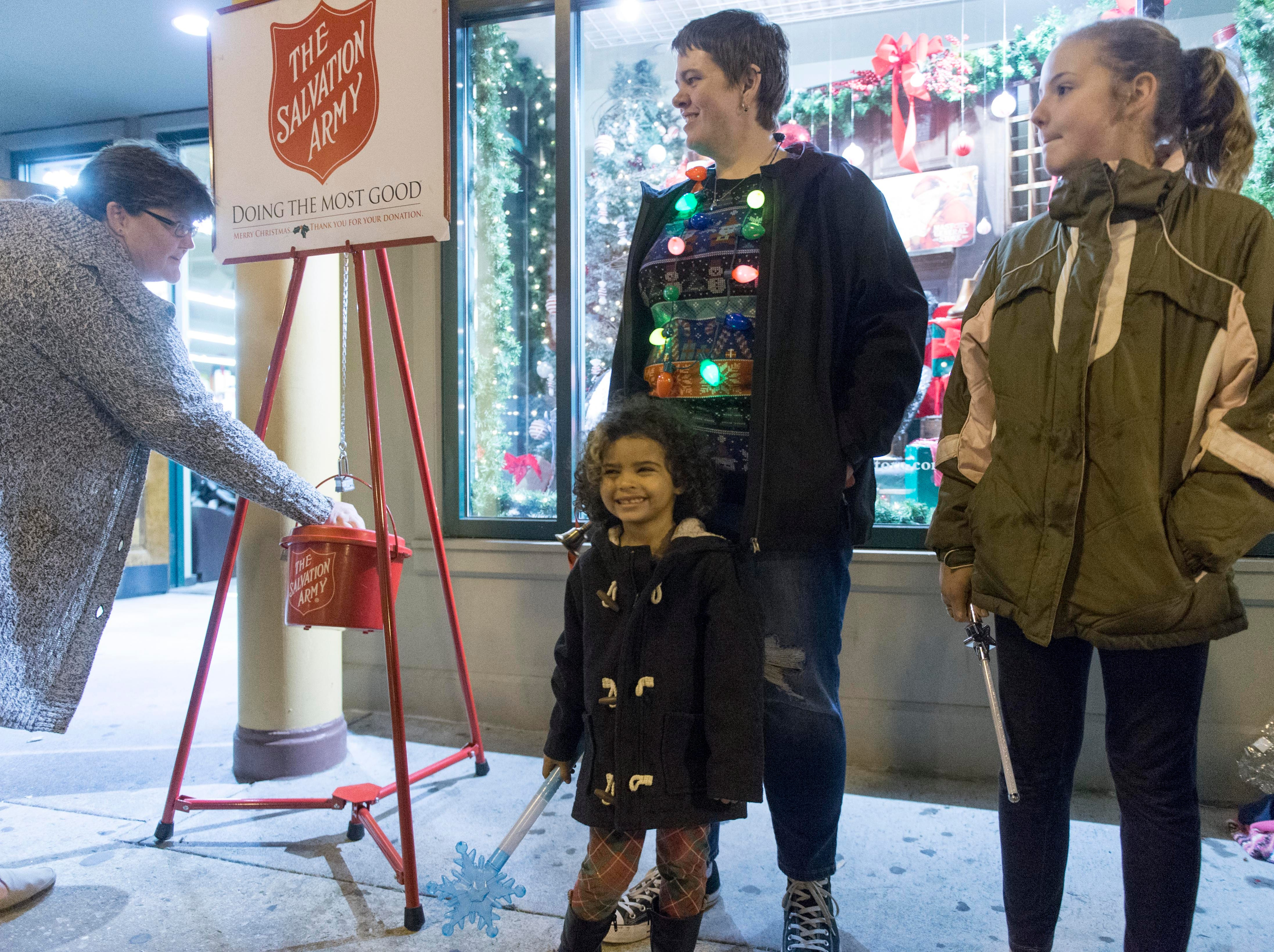 Ruth Ballinger and daughters Alixandria and McKinsey help collect donations for the Salvation Army in Downtown Knoxville on Friday, November 25, 2016 during the Christmas in the City kick-off celebration.