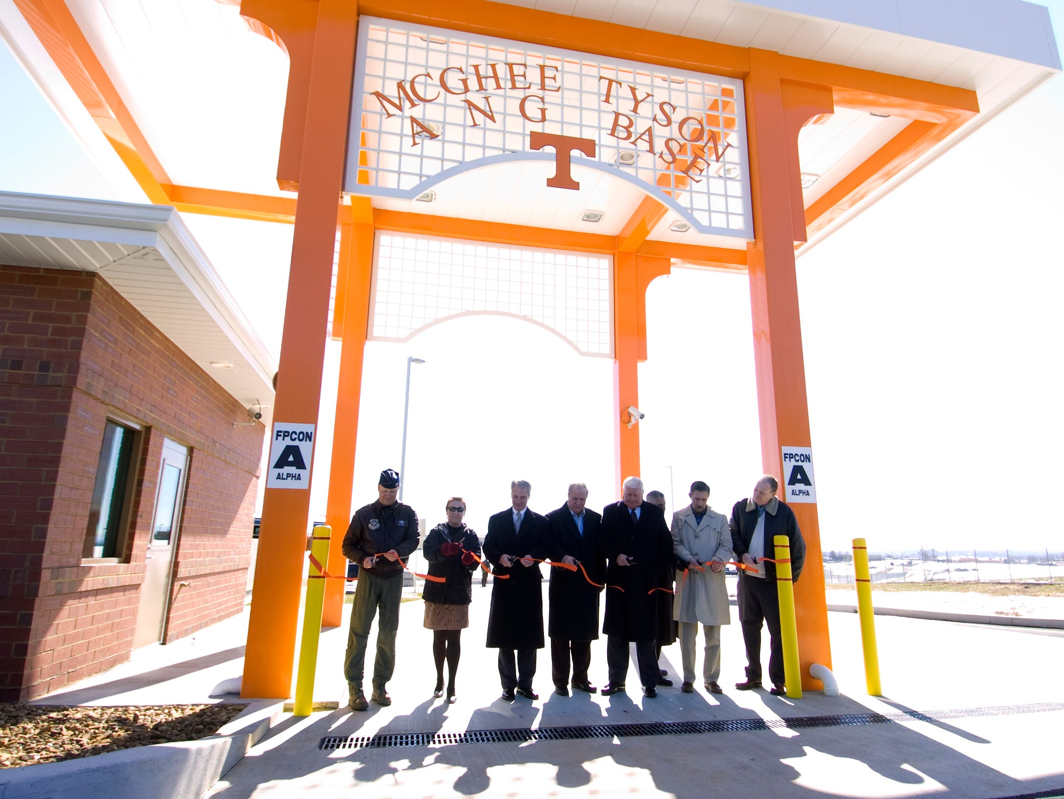 From left, Col. Tim Dearing (cq), Tammy Easterday (cq), Mike Ragsdale (cq), Don Mull (cq), Jerry Cunningham (cq), Chris Soro (cq), Bill Dunlap (cq) and Bill Marrison (cq) participate in a ribbon cutting ceremony to dedicate the new security gate at the McGhee Tyson Air National Guard Base Thursday, February 5, 2009.