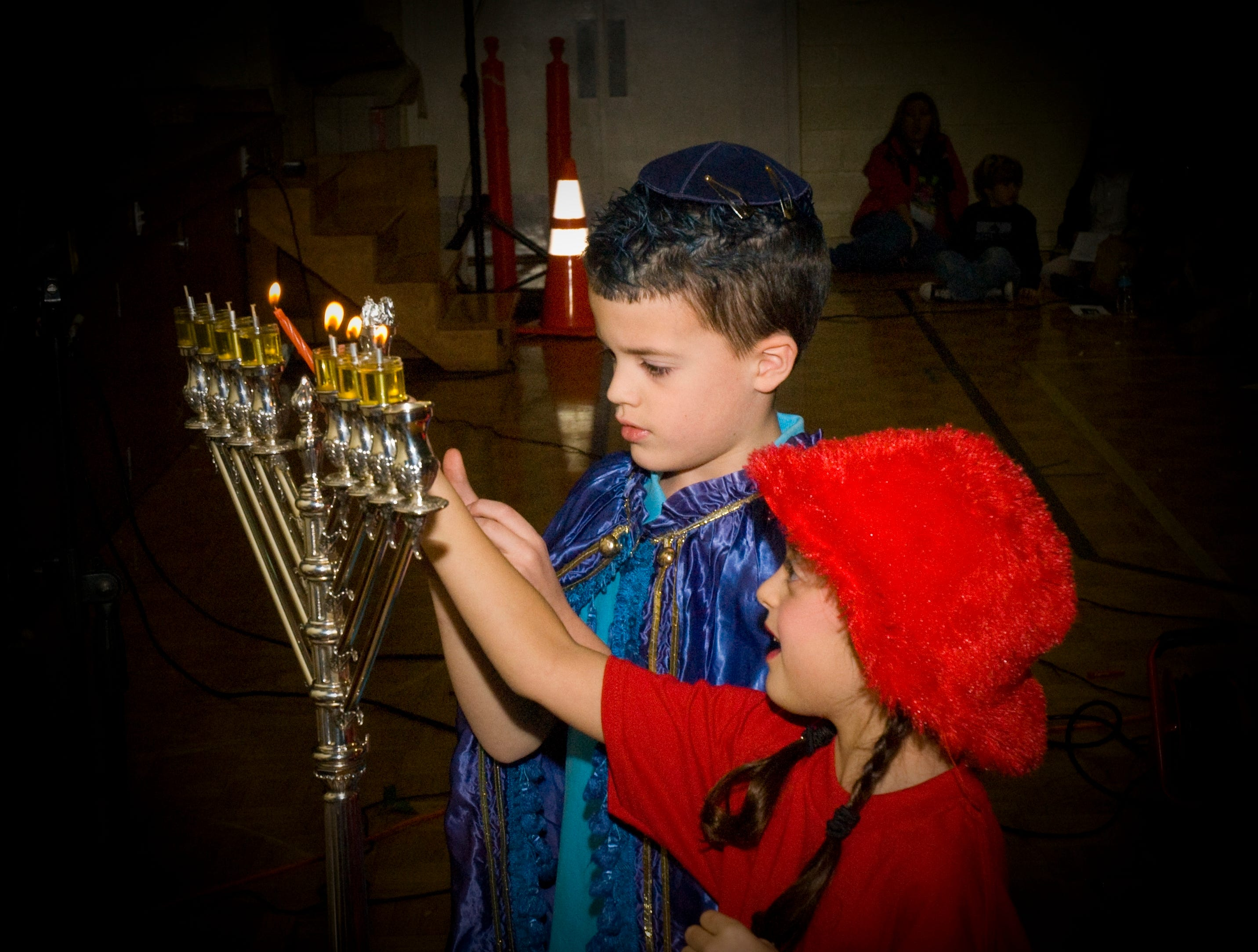Lighting the Menorah at Knoxville Jewish Day School are third-graders Jacob Hale and Yuval Koenig.