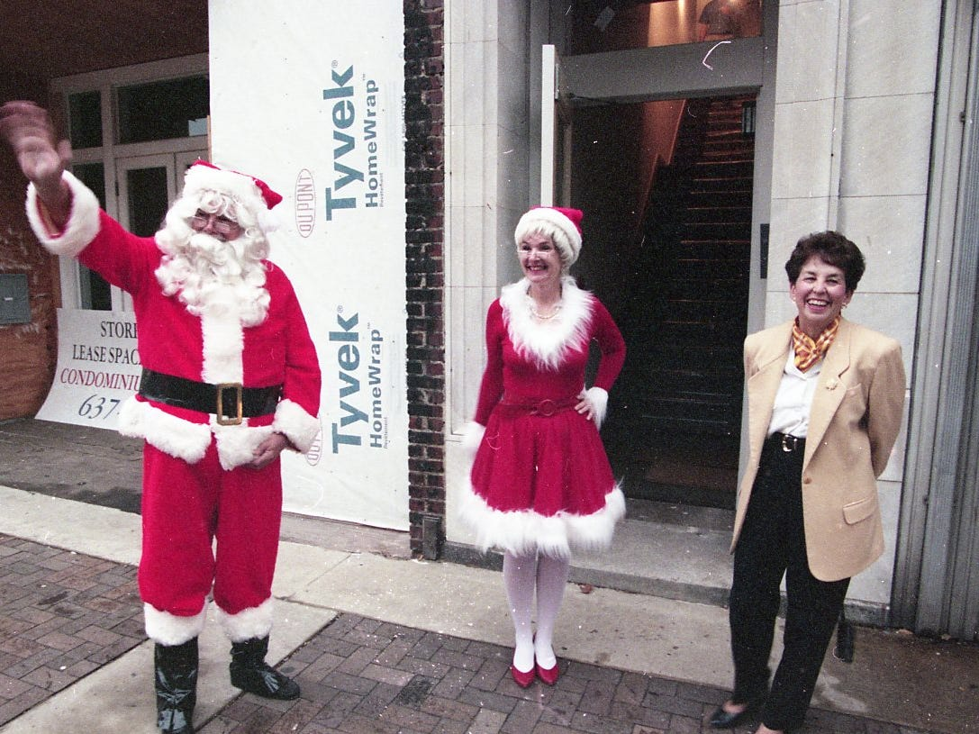Dick and Myra Franklin, dressed as Mr. and Mrs. Santa Claus, wave at passing motorists while waiting for guests to arrive at their Gay St. home in October 1997.