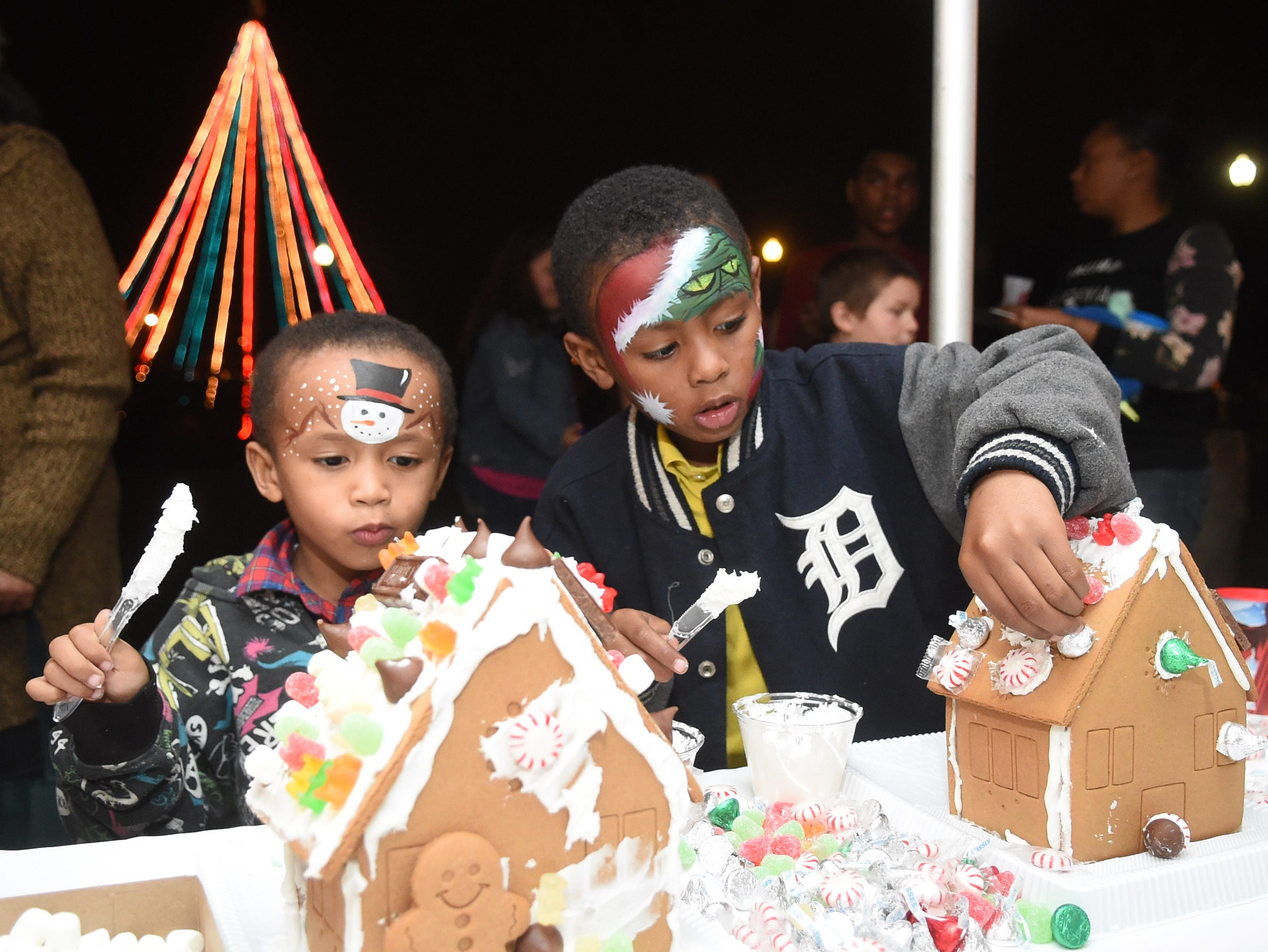 Larryion Boatwright, 4, and Dallas Boatwright, 6, from left, decorate gingerbread houses during Xfinity Christmas at Chilhowee Park on Friday, Dec. 11, 2015. The event offered marshmallow roasting, train rides, and photos with Santa Claus.