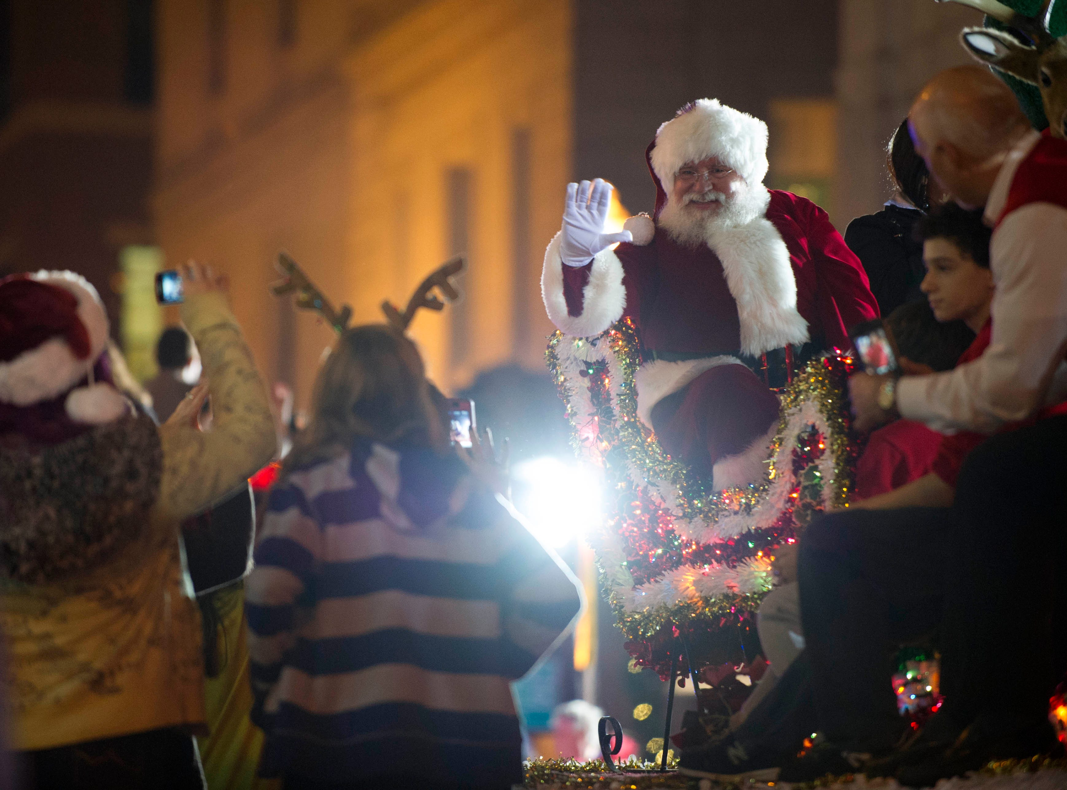 Santa Claus waves to paradegoers during the Christmas parade on Gay Street downtown Friday, Dec. 7, 2012.