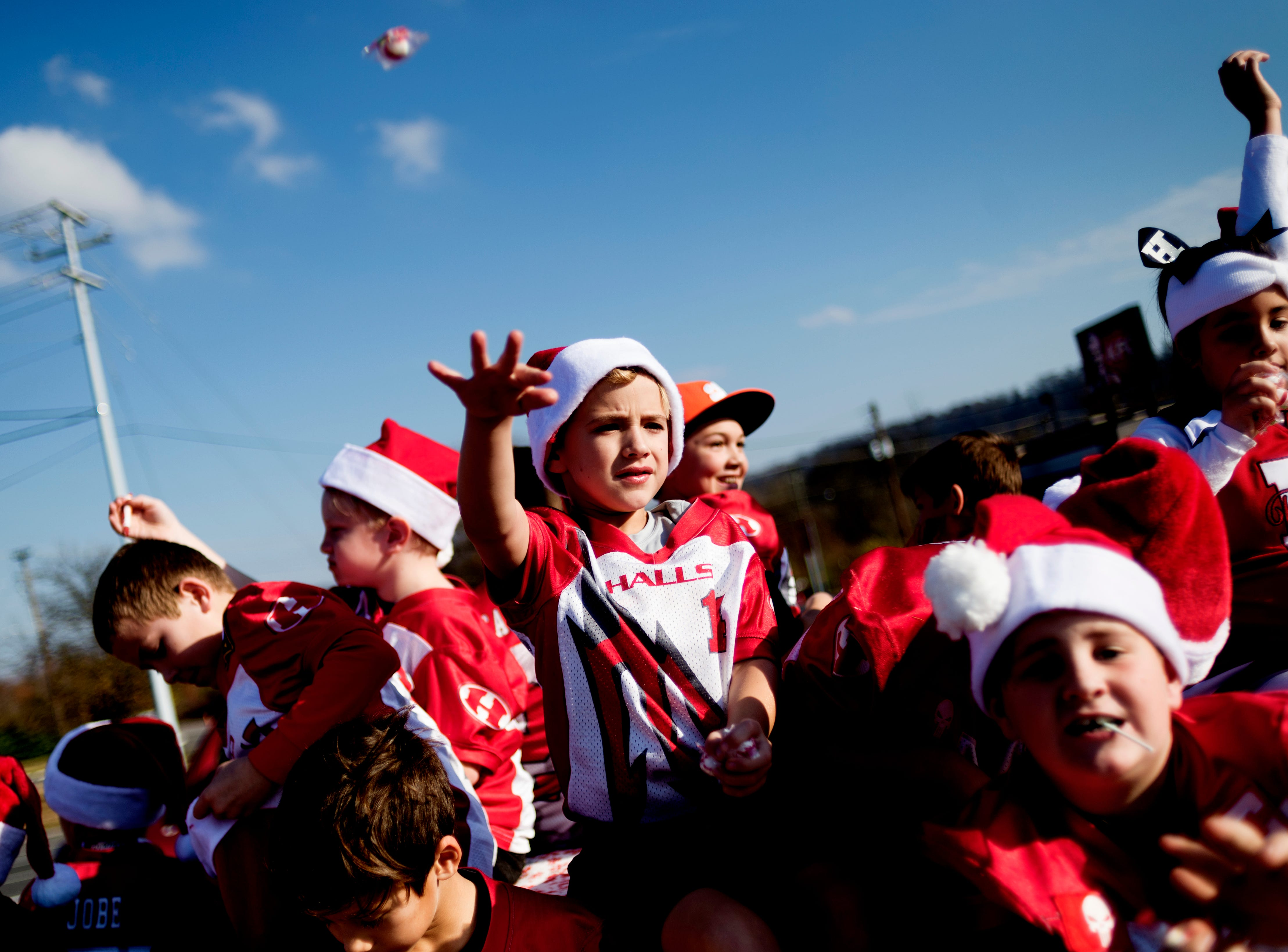 A parade member throws candy to the spectators during the annual Halls Christmas parade along Maynardville Highway in Halls, Tennessee on Saturday, December 2, 2017.