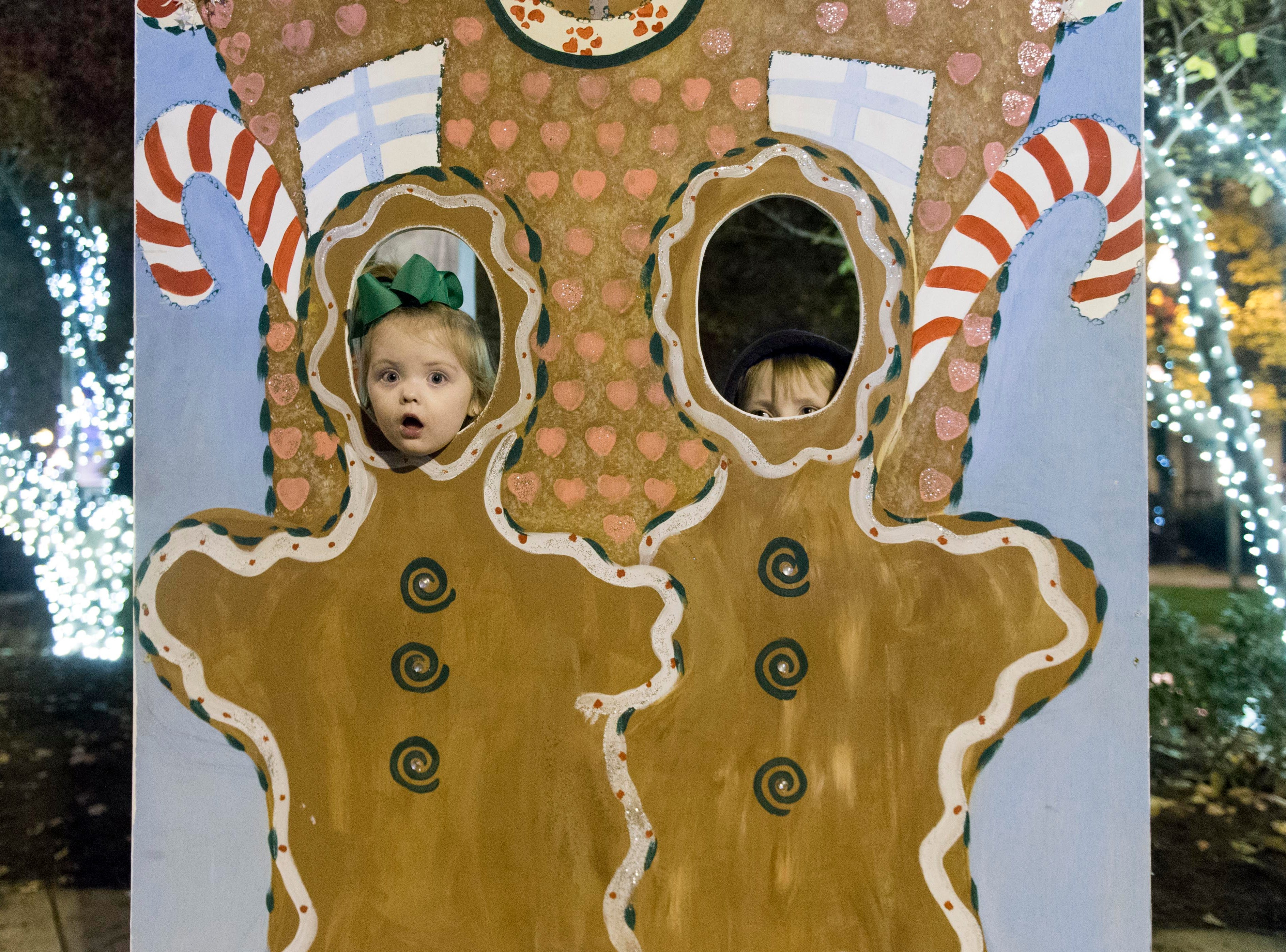 Henley Doss shows herself through a cutout as her brother   Braylen peeks through the hole at the City of Knoxville's Christmas in the City kick-off celebration.