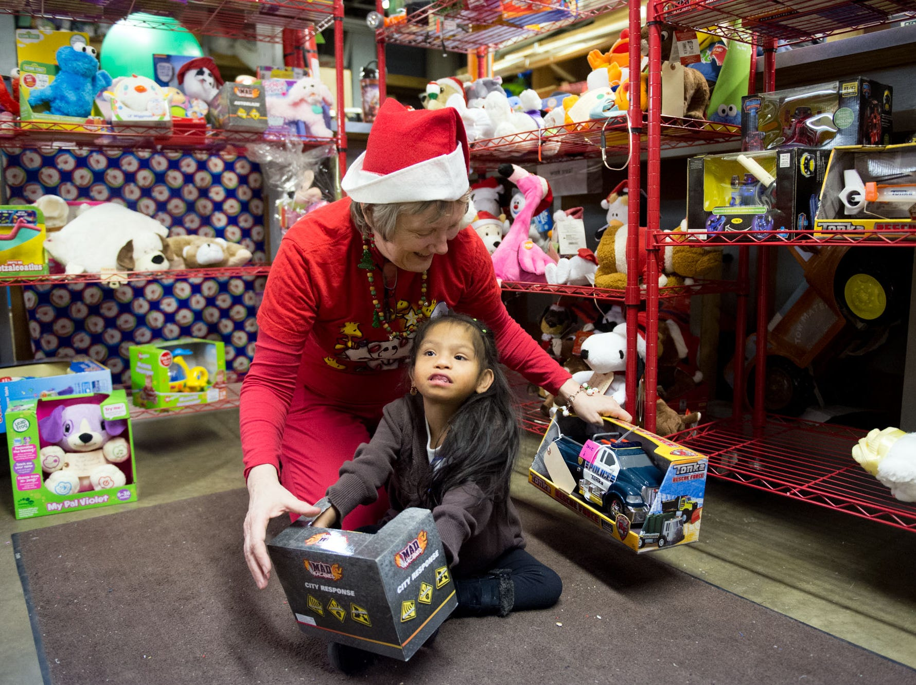 Volunteer Alice Wershing helps Lucy Mendilla, 5, pick out a toy during the East Tennessee Technology Access Center's Toy Tech party on Monday, December 8, 2014. The event gives out electronic toys that have been adapted to be easier to use by children with disabilities.