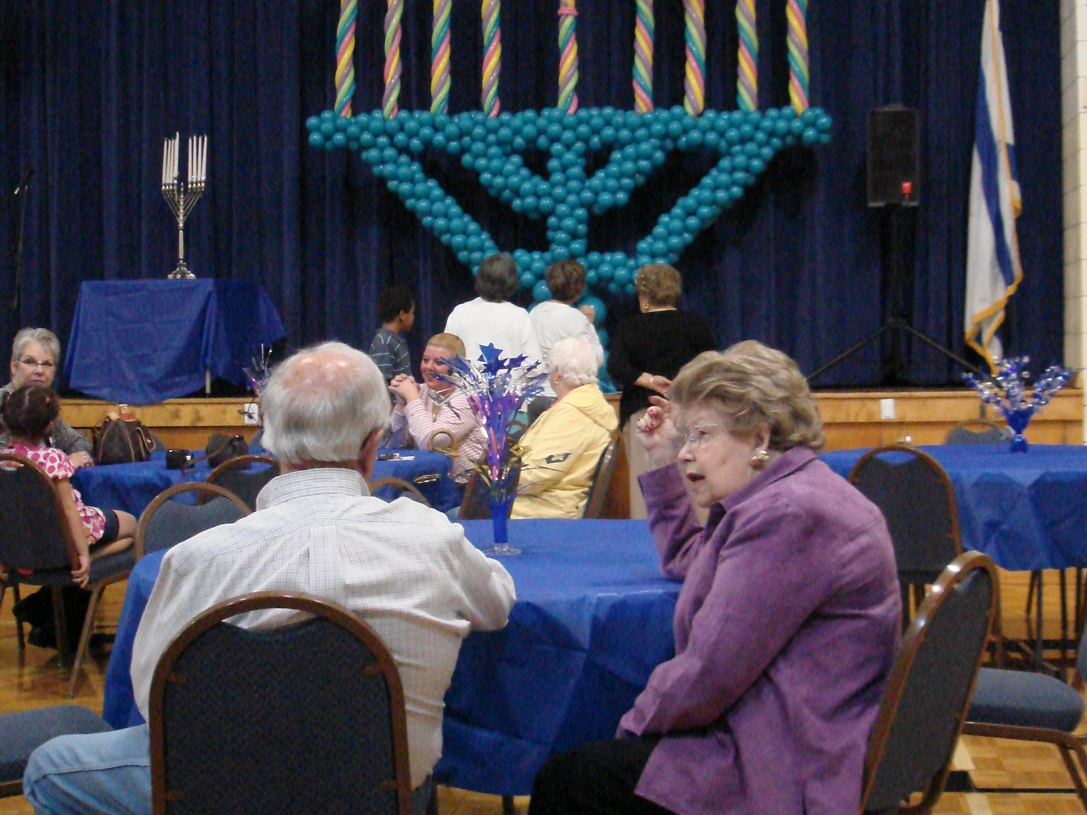 """The construction of a larger than life Menorah by Dianna Glandon, Above the Rest Balloon Designs, sparked favorable comment at the first Menorah Madness celebration, sponsored by the Knoxville Jewish Alliance and Chabad of Knoxville and held in the gymnasium of the Arnstein Jewish Community Center on Dec. 11. Eleanor Shorr, foreground, described her reaction in one word: """"magnificent."""""""