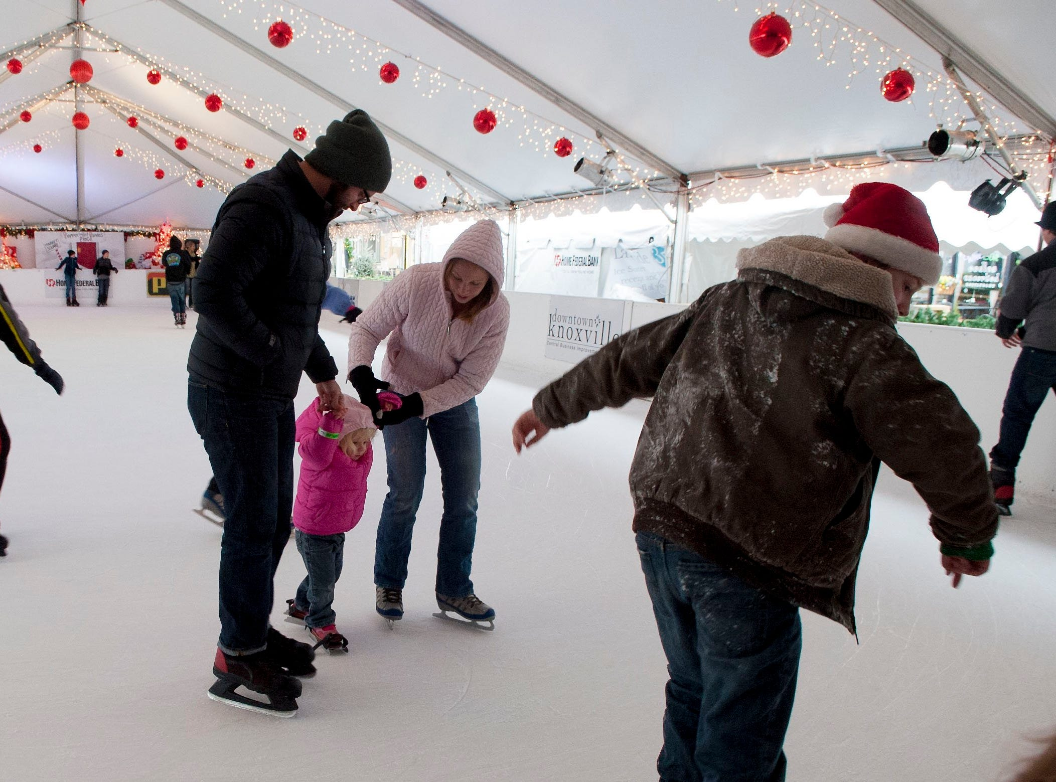 Joseph and Johanna Luncford help their tow year old daughter McKinley Luncford navigate the ice at the  outdoor ice skating rink on Market Square in downtown Knoxville Tuesday December 24, 2013.Knoxville's Holidays on Ice, is an outdoor ice skating rink on Market Square in downtown Knoxville.  Skaters can enjoy the ice under a tent with Christmas lights rain or shine.  The skating rink will be closed Christmas Day but will be open till January 5, 2014.