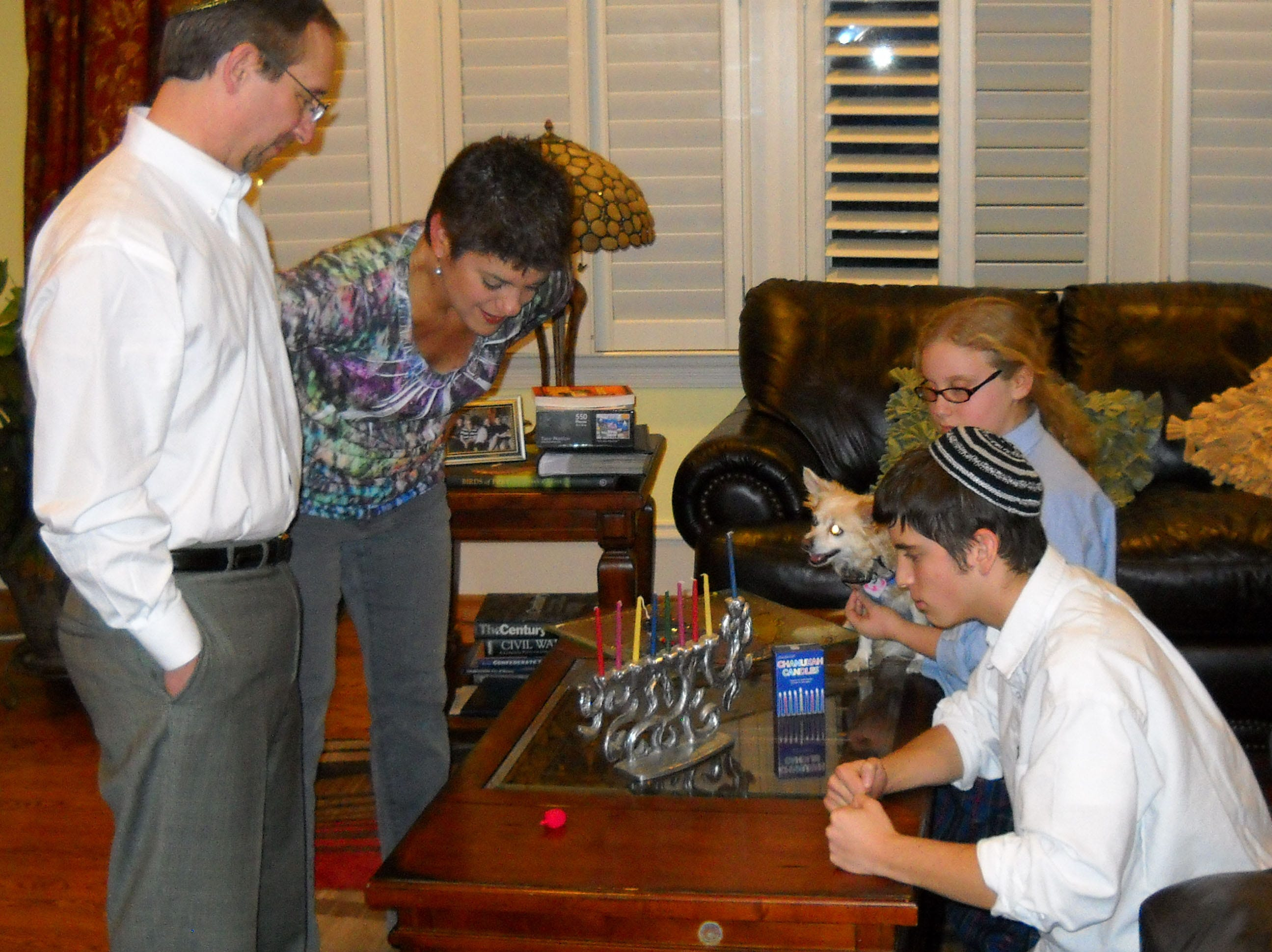 Michael Dryzer spins the dreidel, a four-sided top used in a game during the Hanukkah season, while his family watches.