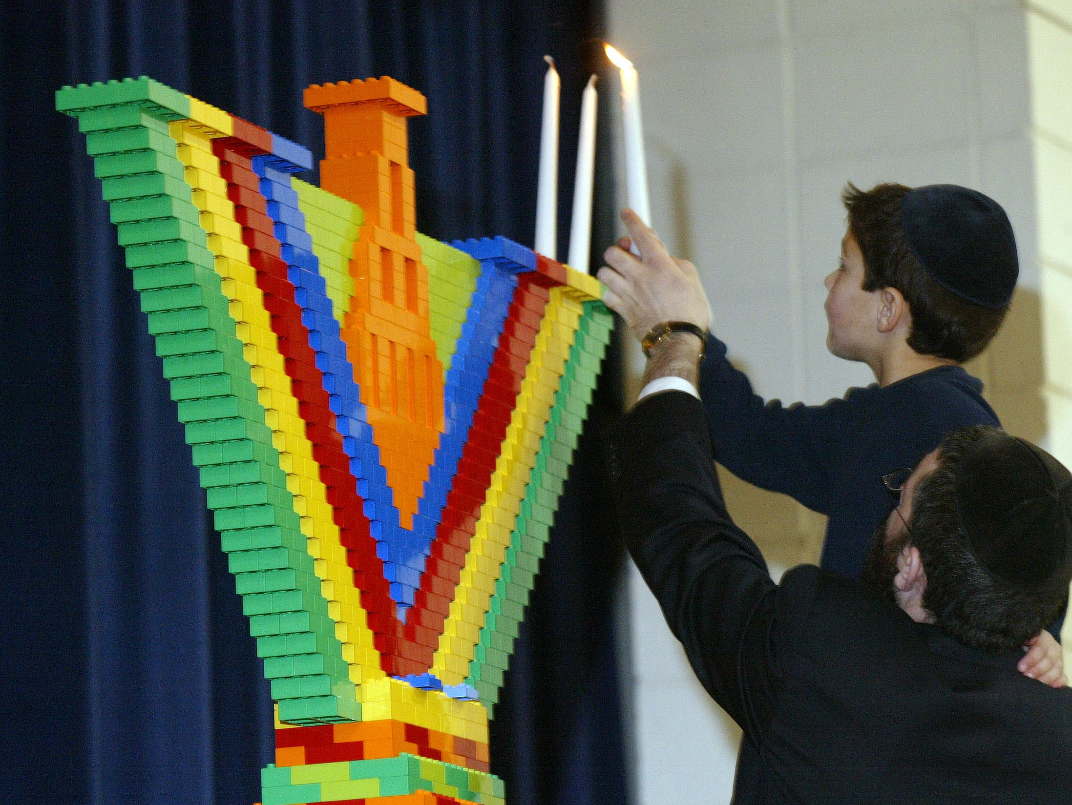 Because his birthday falls on Dec. 25, which is the beginning of Hanukkah, Yakov Drumm, 6, of Knoxville helped Rabbi Yossi Wilhelm light the 10-foot menorah built with building blocks by children at the Arnstein Jewish Community Center. 12/26/05