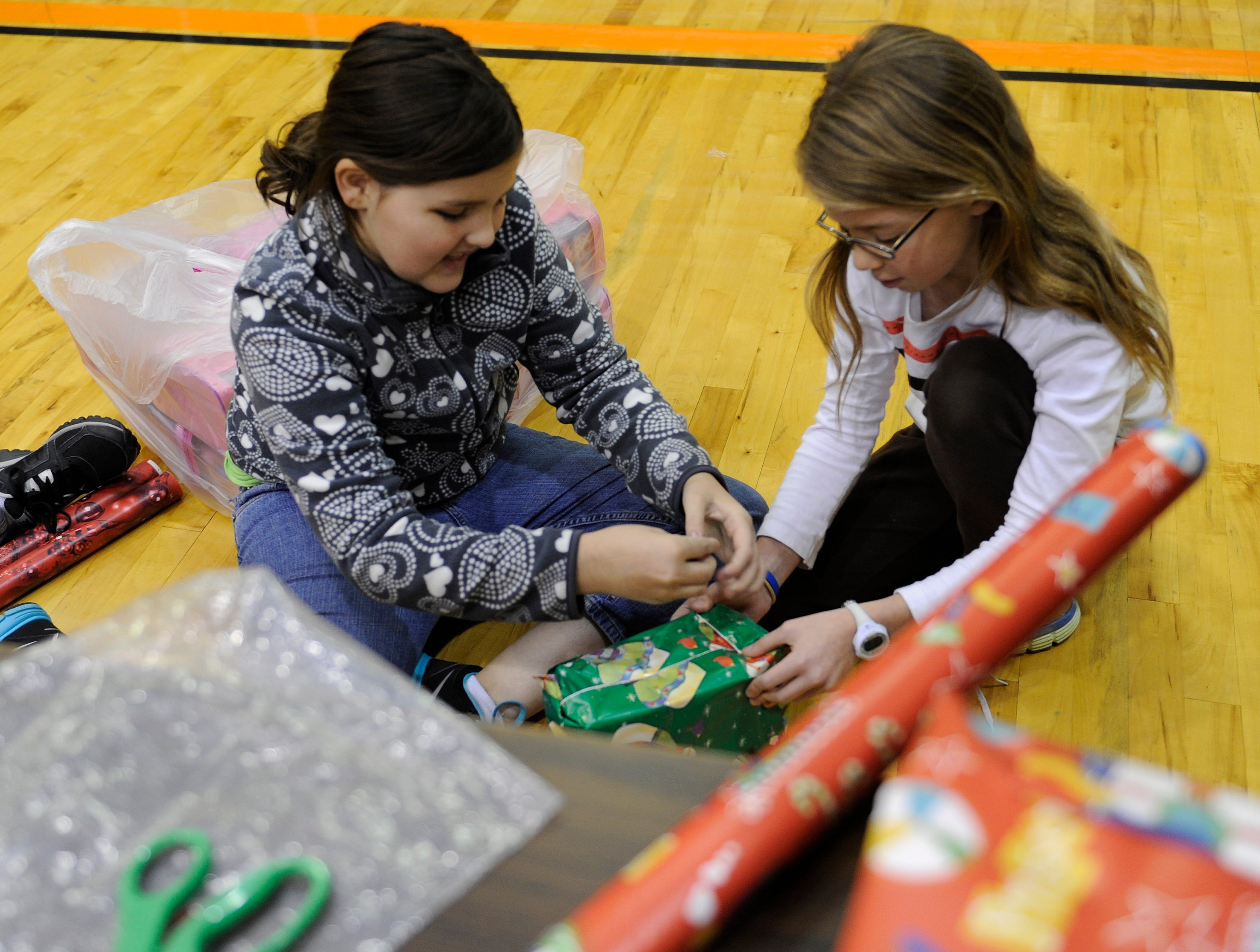 Hally Mills, left, and Ashley Teaster, right, wrap presents for the Knoxville Inner City Kids Outreach Christmas gift program at Park West Church, Saturday, Nov. 25, 2012.