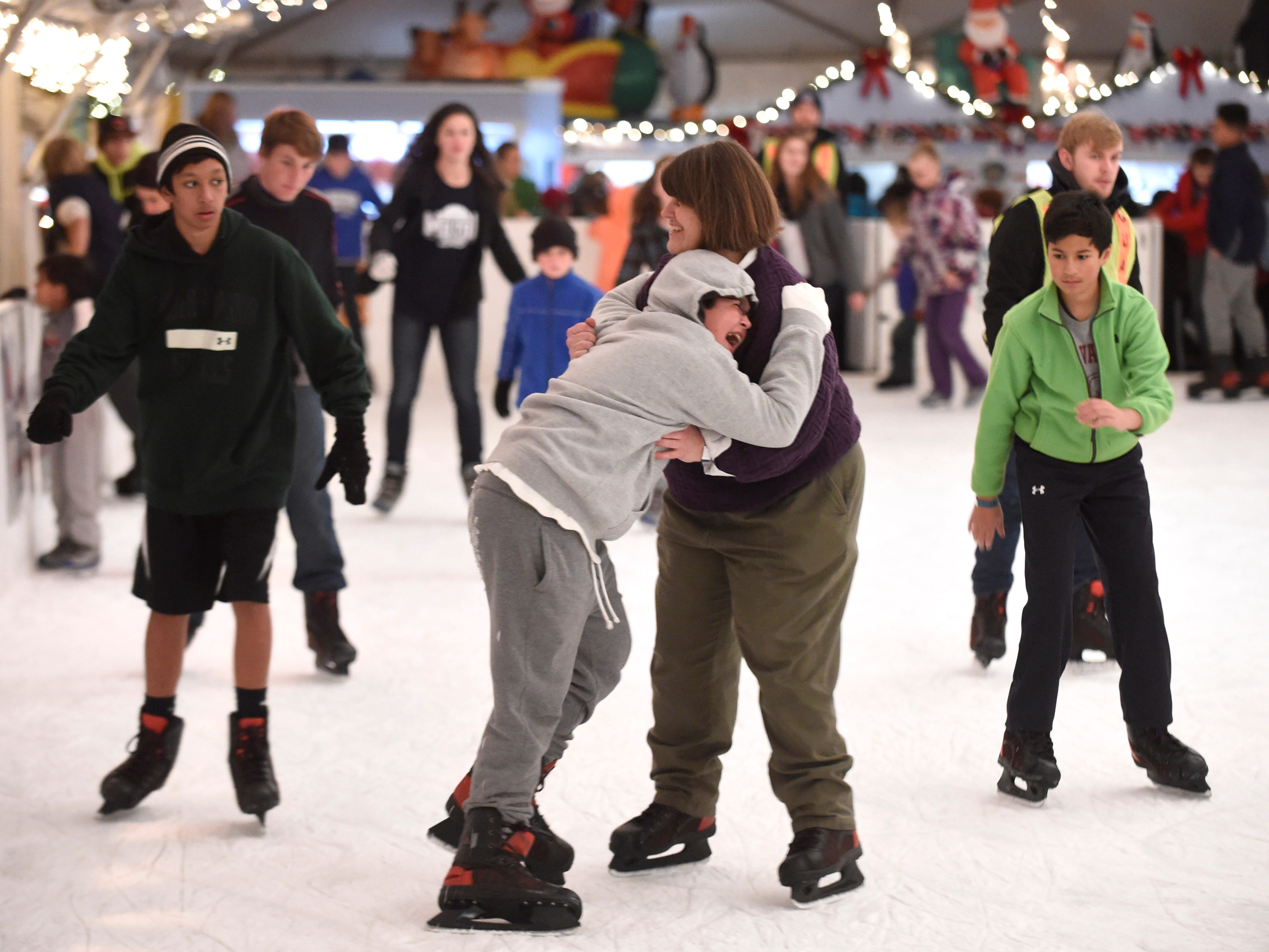 John Robert Boyd, 11, laughs while clinging to Karen Boyd in hopes of avoiding a fall on the ice rink in Market Square during Christmas in the City festivities in downtown Knoxville on Friday, Nov. 28, 2014.