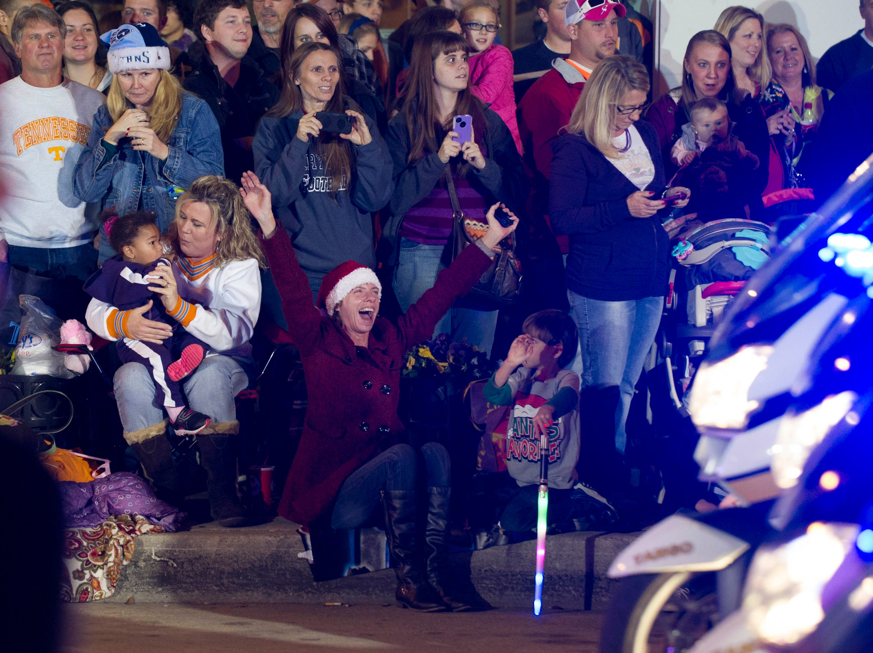 Paradegoers watch as Tennessee Highway Patrol motorcycles kick off the Christmas parade on Gay Street downtown Friday, Dec. 7, 2012.