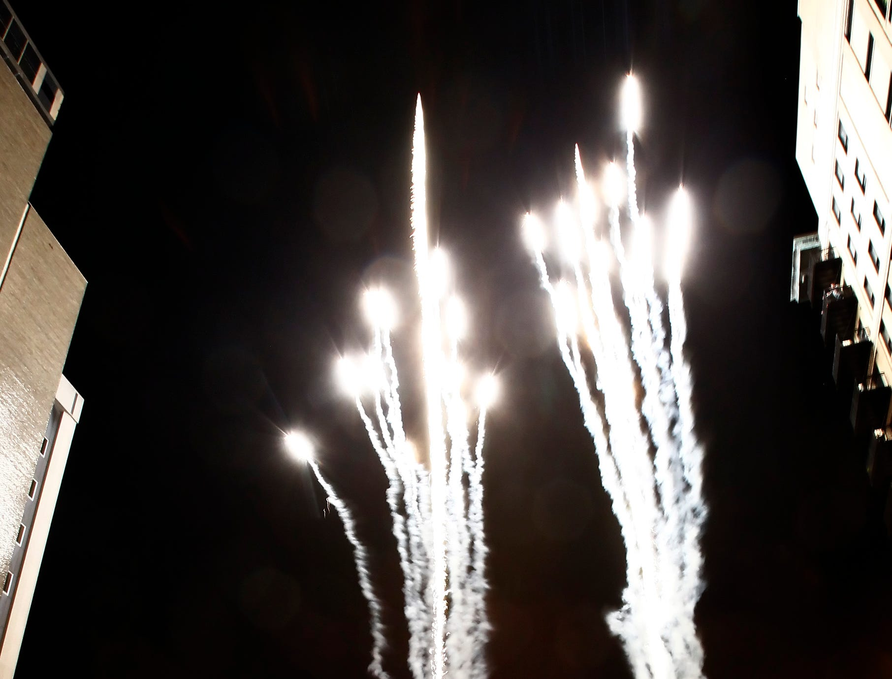 People watch as fireworks explode during the lighting of the Christmas tree at Market Square Friday, Nov. 25, 2011.