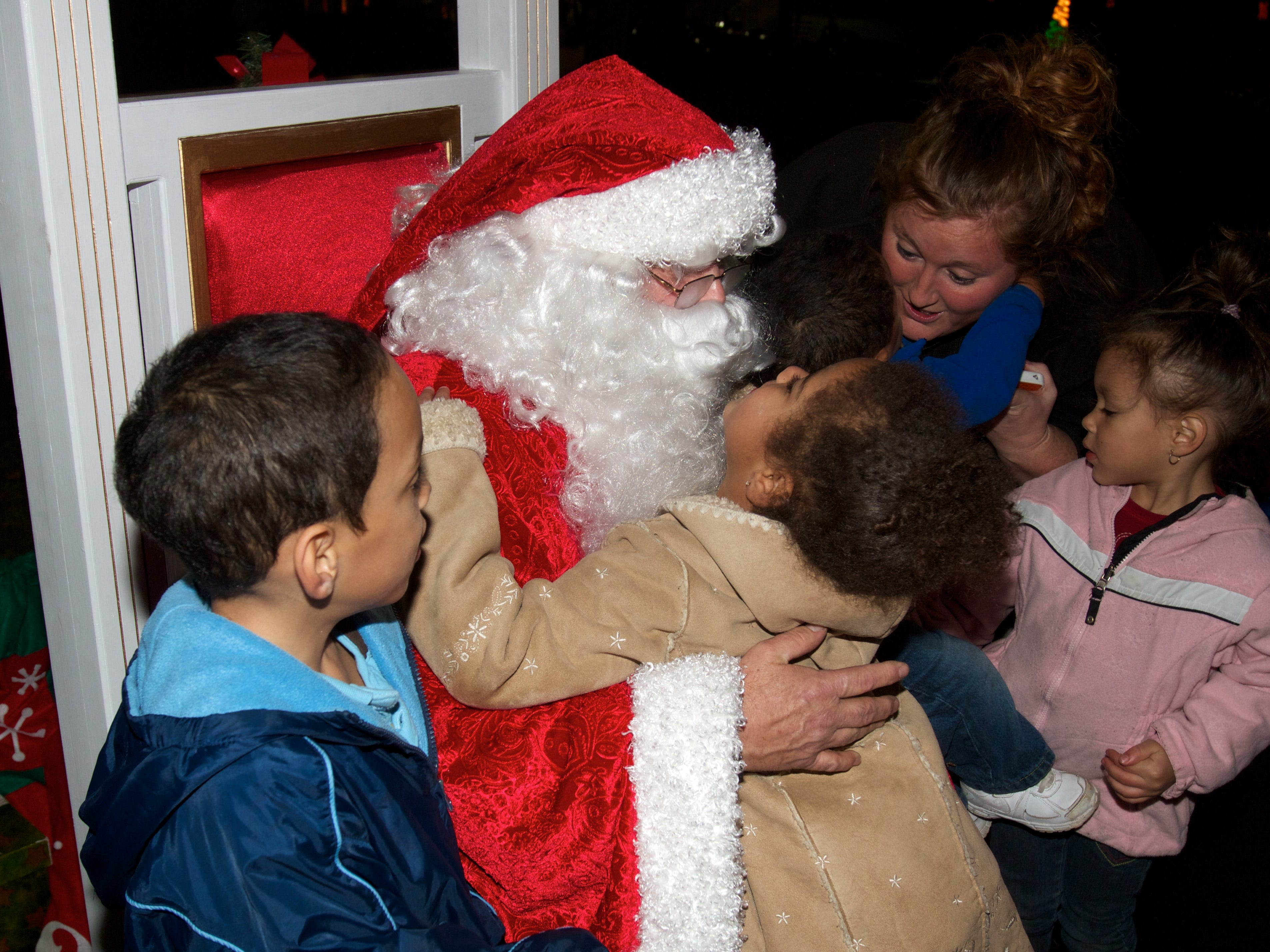 Visiting Santa are, from left, Darius Dawson, 6, Hazel Greymount, 5, Julian Cabage, 1, Tonya Cabage and Serenity Dawson, 4, on Friday, November 30, 2012 during Comcast Christmas at Chilhowee Park.