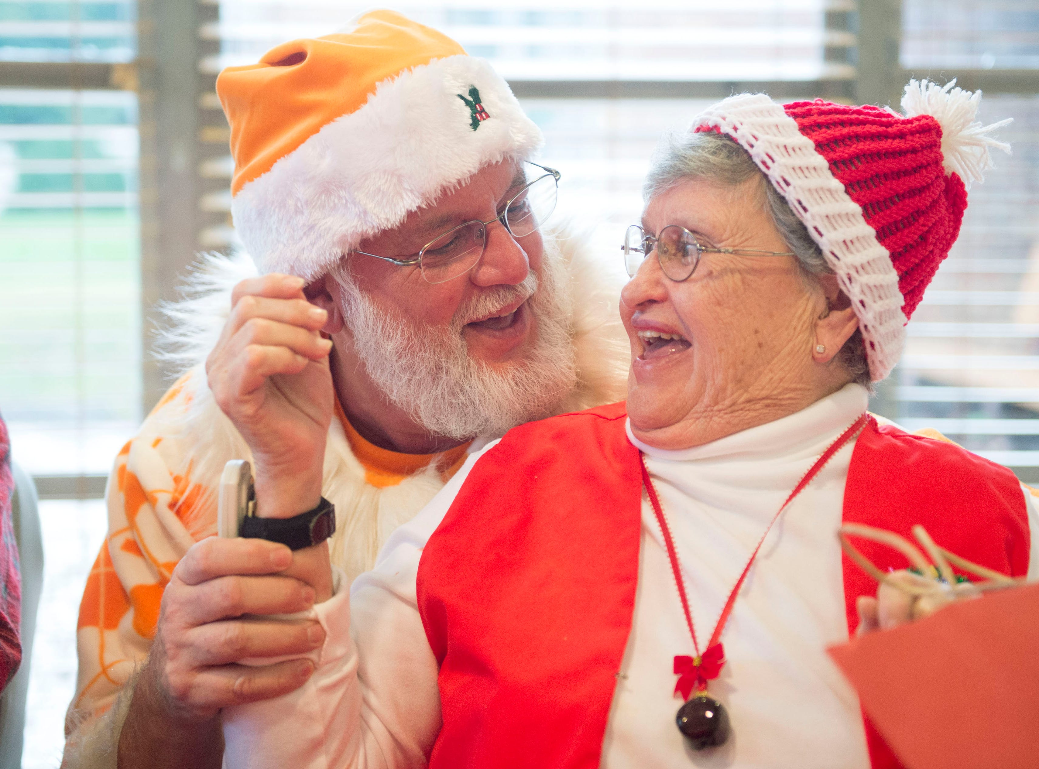 Bruce Farrant greets Elizabeth Franklin during a holiday party at the Asbury Place assisted living facility on Wednesday, December 23, 2015. Farrant wears an orange Tennessee Volunteer Santa outfit that was made by Franklin for the event.