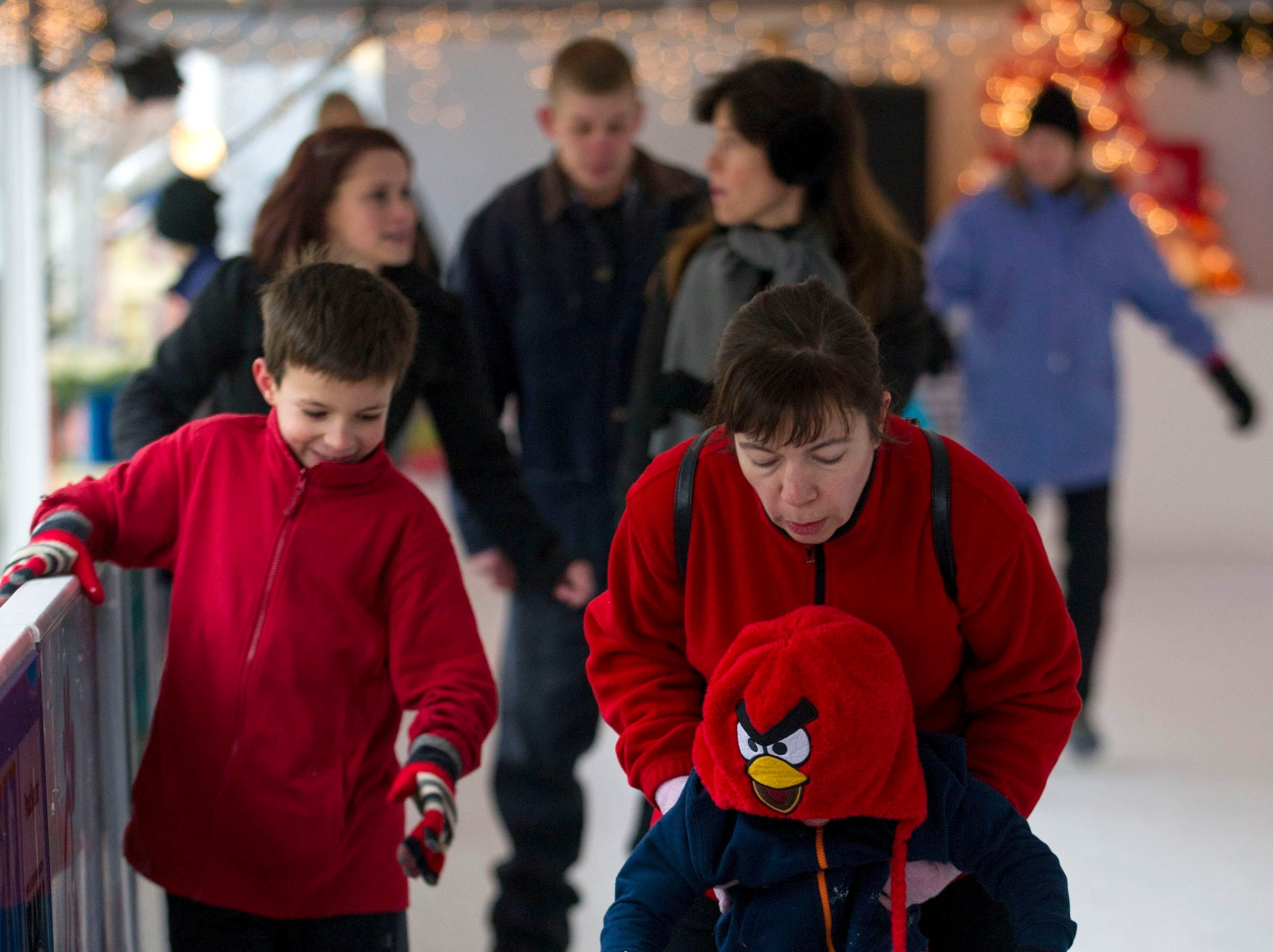 Aimee Ward helps her son Jake Ward, 4, learn to skate at the outdoor ice skating rink on Market Square in Downtown Knoxville on Dec. 24, 2013.