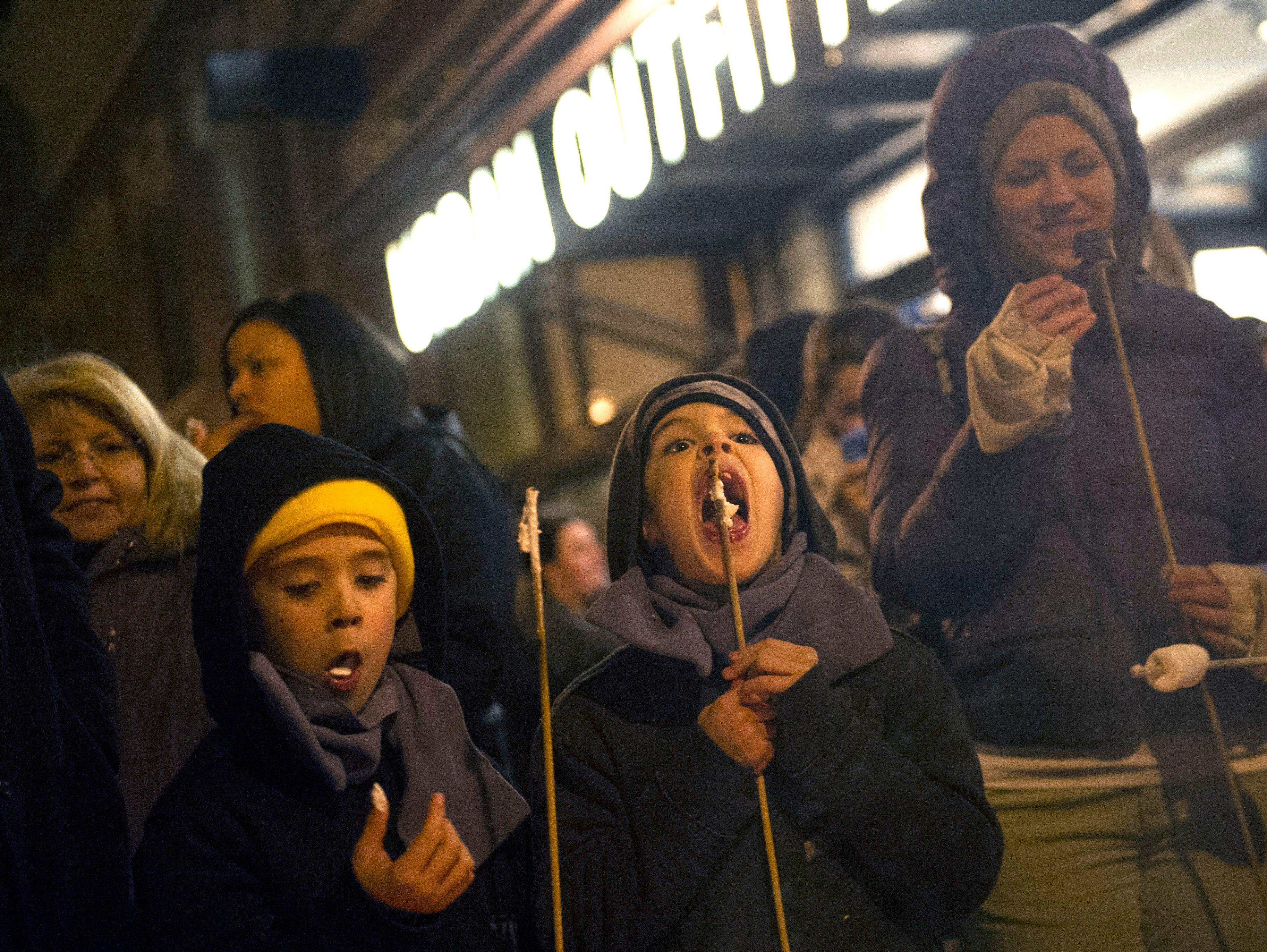 Twin brothers Gage and Drew Keely, both 7, from left, and Stephanie Smith, right, enjoy roasted marshmallows  on the sidewalk near Krutch Park during Christmas in the City festivities in downtown Knoxville on Friday, Nov. 28, 2014.