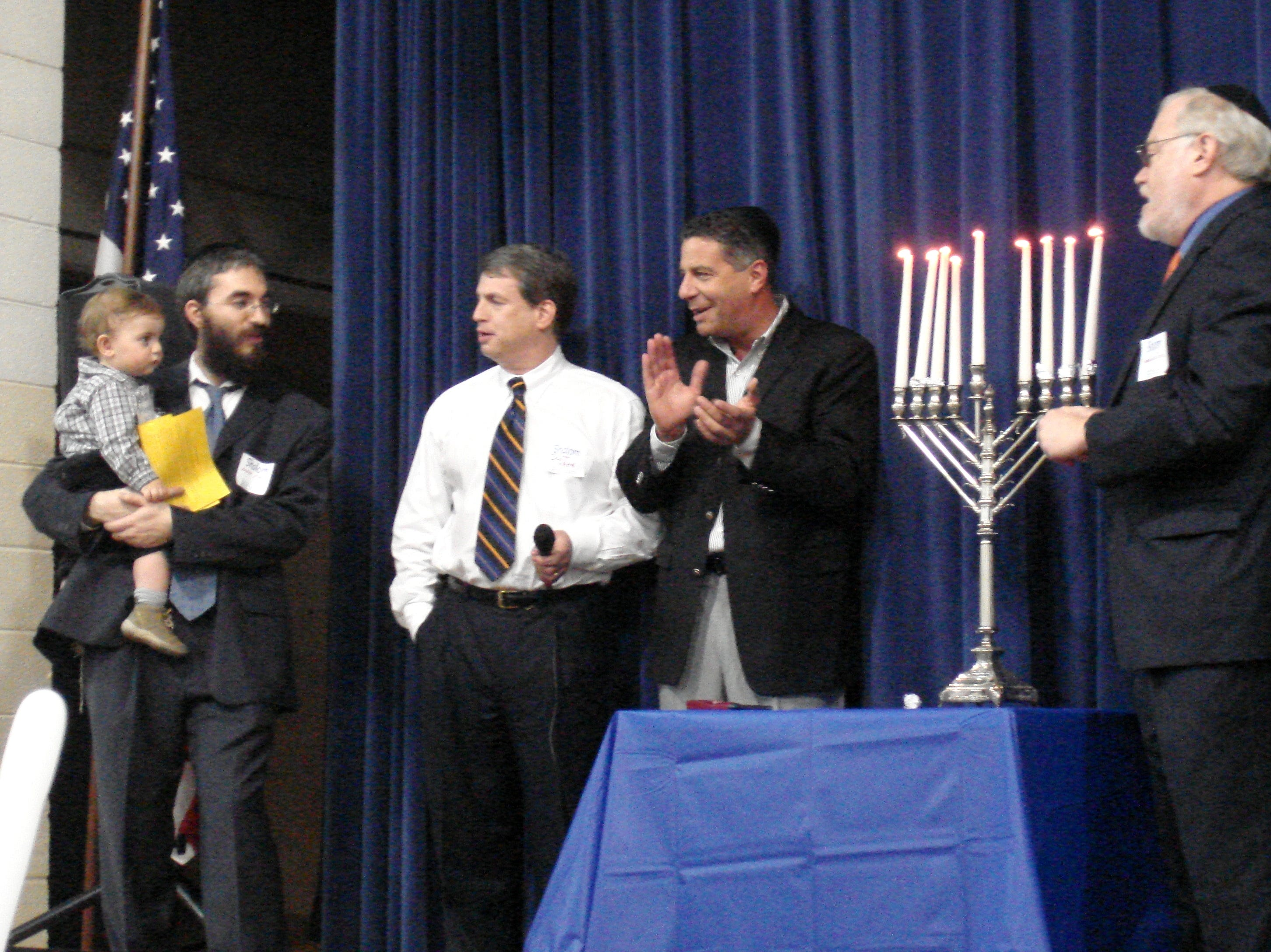 University of Tennessee men's basketball coach Bruce Pearl, fourth from left, claps his hands while singing a traditional Chanukah melody following his lighting of the Menorah during the Menorah Madness celebration held Dec. 11 at the Arnstein Jewish Community Center. From left are Rabbi Yossi Wihelm, holding his son Mendel, Scott Hahn, Pearl and Rabbi Louis Zivic.
