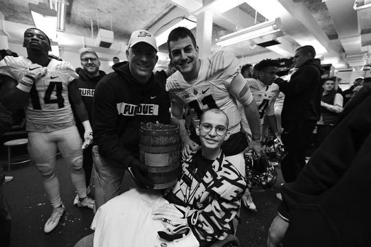Tyler Trent sits next to Purdue football coach Jeff Brohm and quarterback David Blough after Purdue beat Indiana to win the Old Oaken Bucket on Nov. 24, 2018.