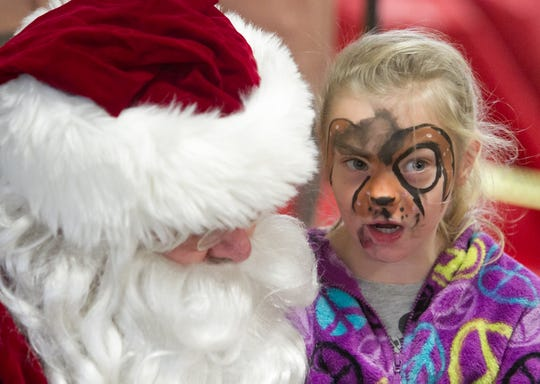 """7-year-old Aubrey Foreman asks Santa for a fart gun like those depicted in the movie """"Despicable Me"""" in the Fowlerville Fire Station Saturday, Dec. 2, 2017 during Christmas in the 'Ville."""