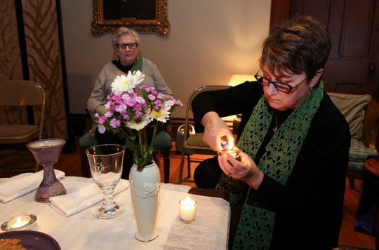 Mary Sue Barnett lights a candle before leading a service at the First Unitarian Church.  She is a woman priest who was ordained by the Association of Roman Catholic Women Priests.  Nov. 26, 2018