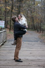 Blake Martin and Shannon Keene celebrate their marriage engagement on a wooden bridge in Louisville's Cherokee Park.