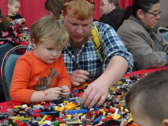 Ben Cox, then 3, left, looks to his father, Nathan, for help with constructing a LEGO vehicle at the Brick Universe LEGO Fan Convention two years ago at the  Kentucky Exposition Center.