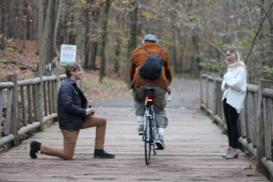 This is the moment a man on a bicycle rides through Blake Martin's marriage proposal to his girlfriend Shannon Keene. Cherokee Park, Louisville, Kentucky.