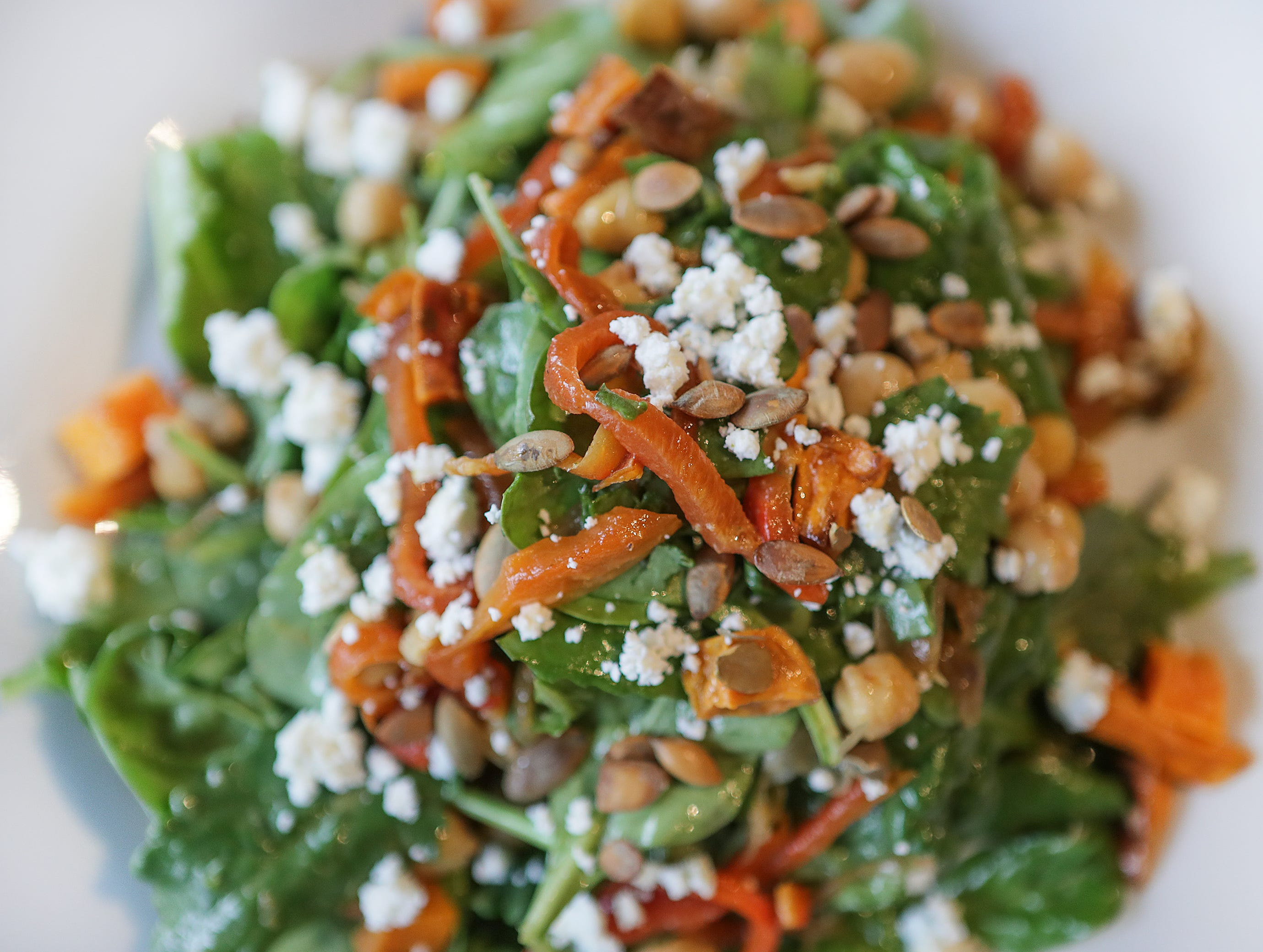 Seasonal Salad featuring salad greens, roasted sweet potatoes, spiced chick peas, goat cheese, toasted pumpkin seeds in herb vinaigrette at Farm To Fork in Portland.